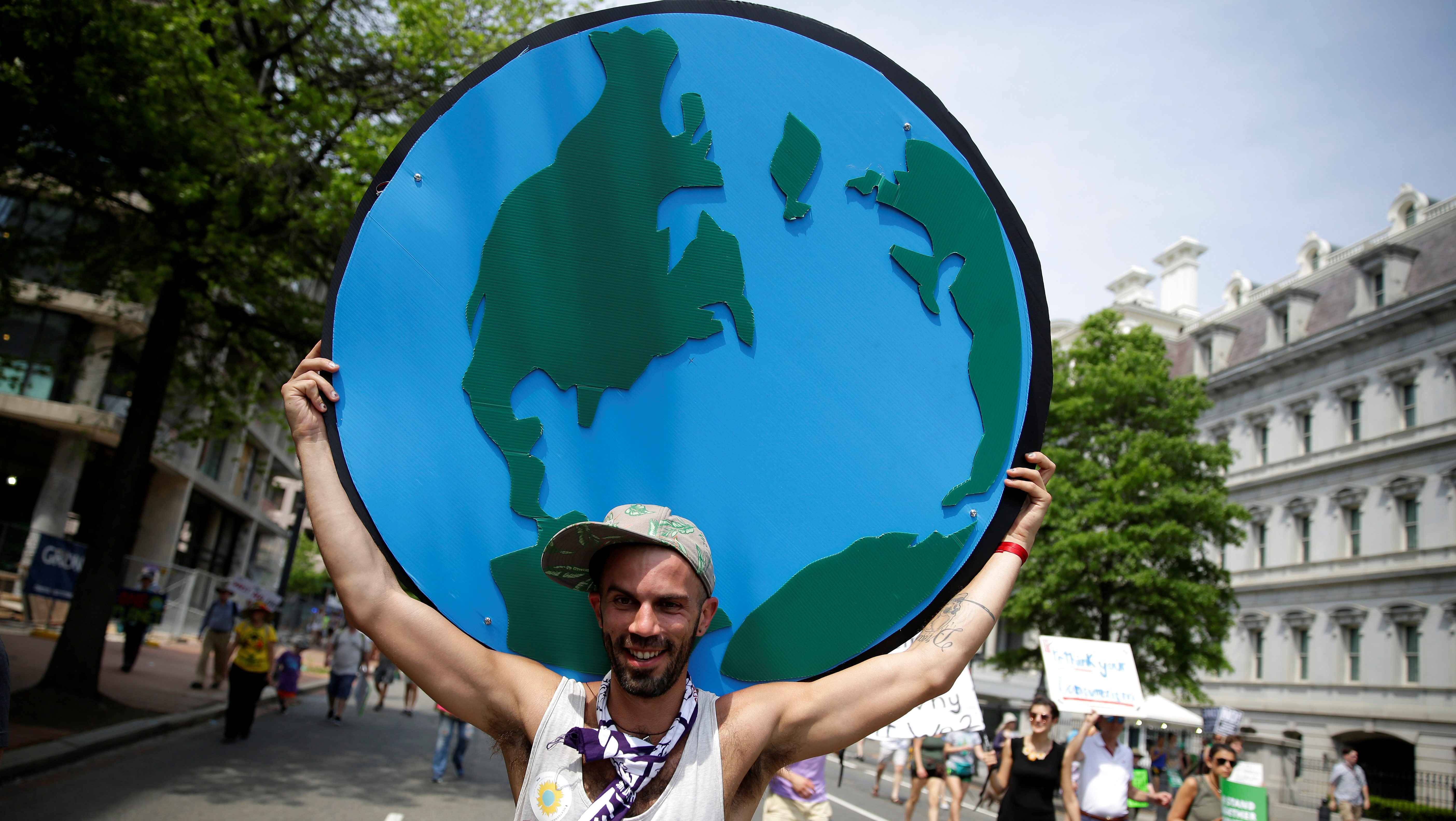 A protester carries a sign depicting the earth during the Peoples Climate March near the White House in Washington, U.S., April 29, 2017.      REUTERS/Joshua Roberts - RTS14HJN