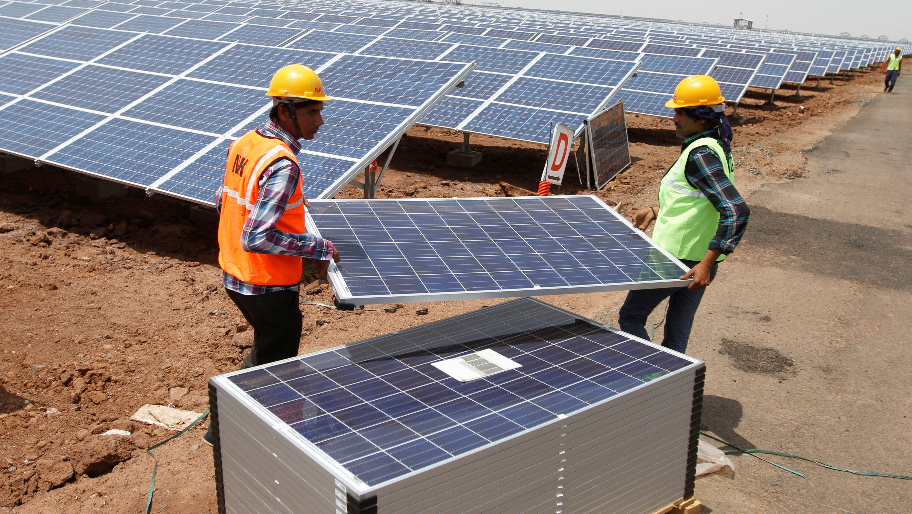 FILE PHOTO: Workers carry photovoltaic solar panels for installation at the Gujarat solar park under construction in Charanka village