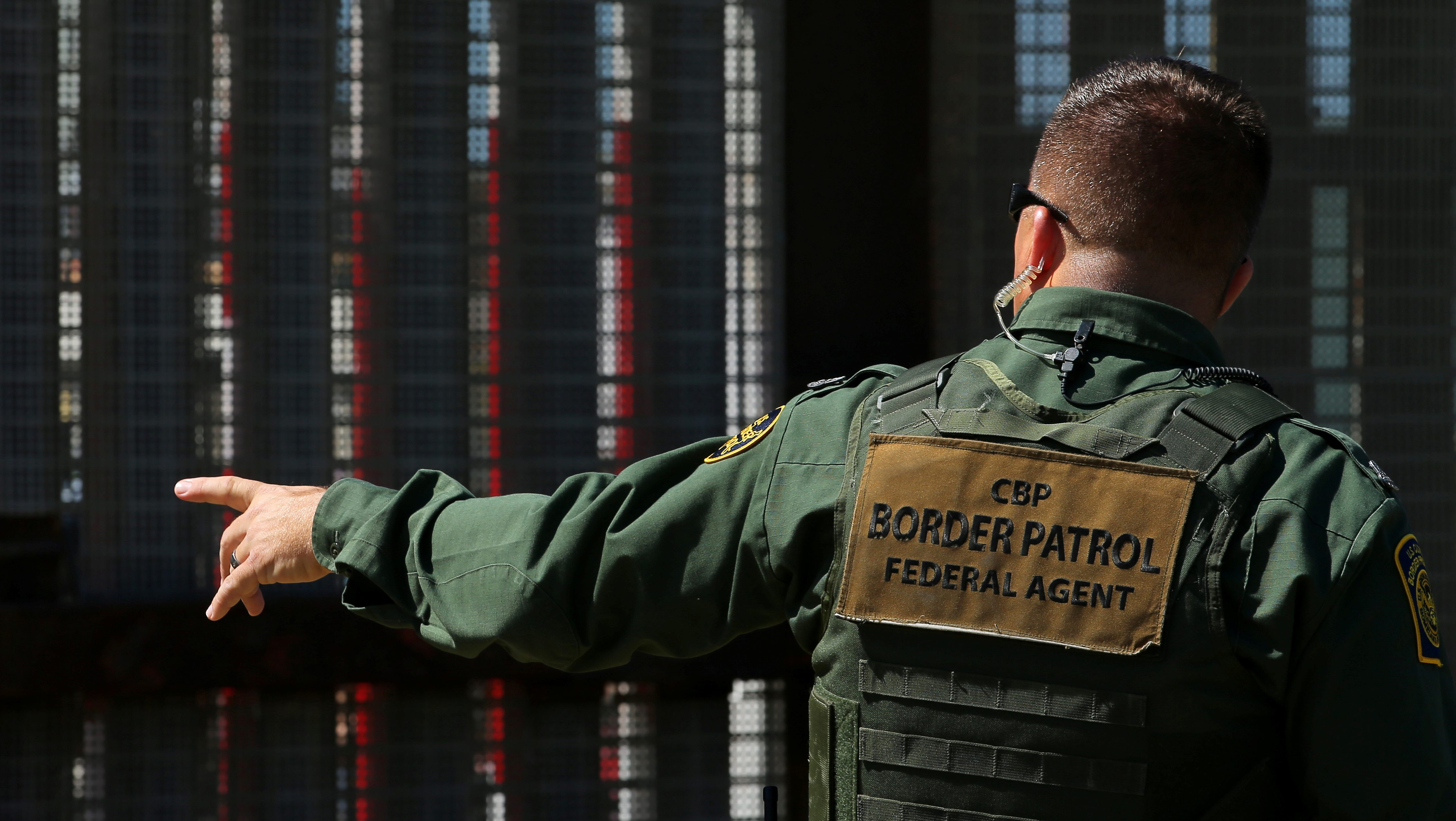A U.S. Border patrol agent directs people near the fence with Mexico during a Children's Day event at Border Field State Park in San Diego, California, U.S., April 30, 2017.   REUTERS/Mike Blake - RTS14L1S