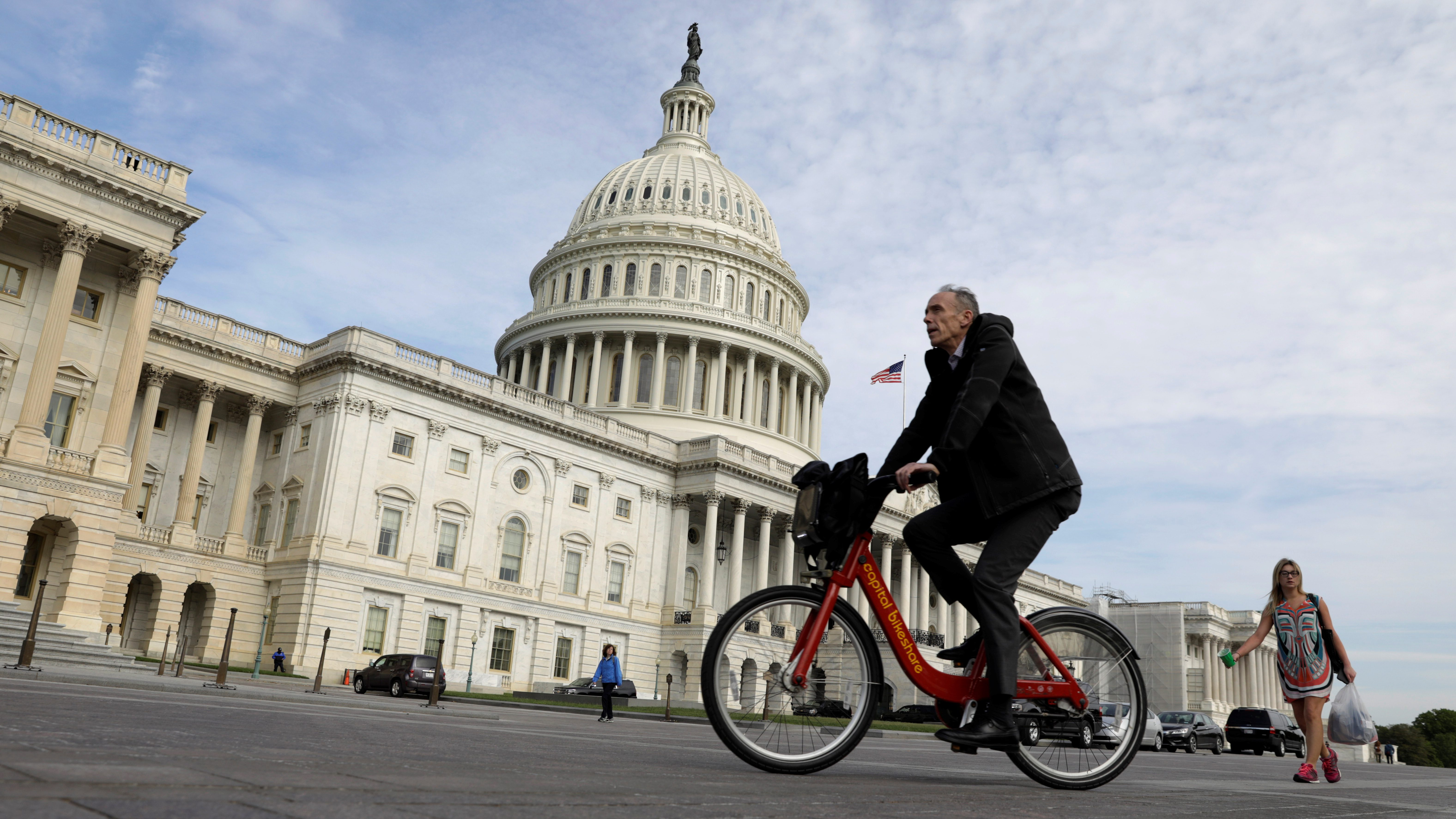 A cyclist passes the the U.S. Capitol, on the day the House is expected to vote here to repeal Obamacare in Washington, D.C., U.S., May 4, 2017. REUTERS/Kevin Lamarque - RTS154YR