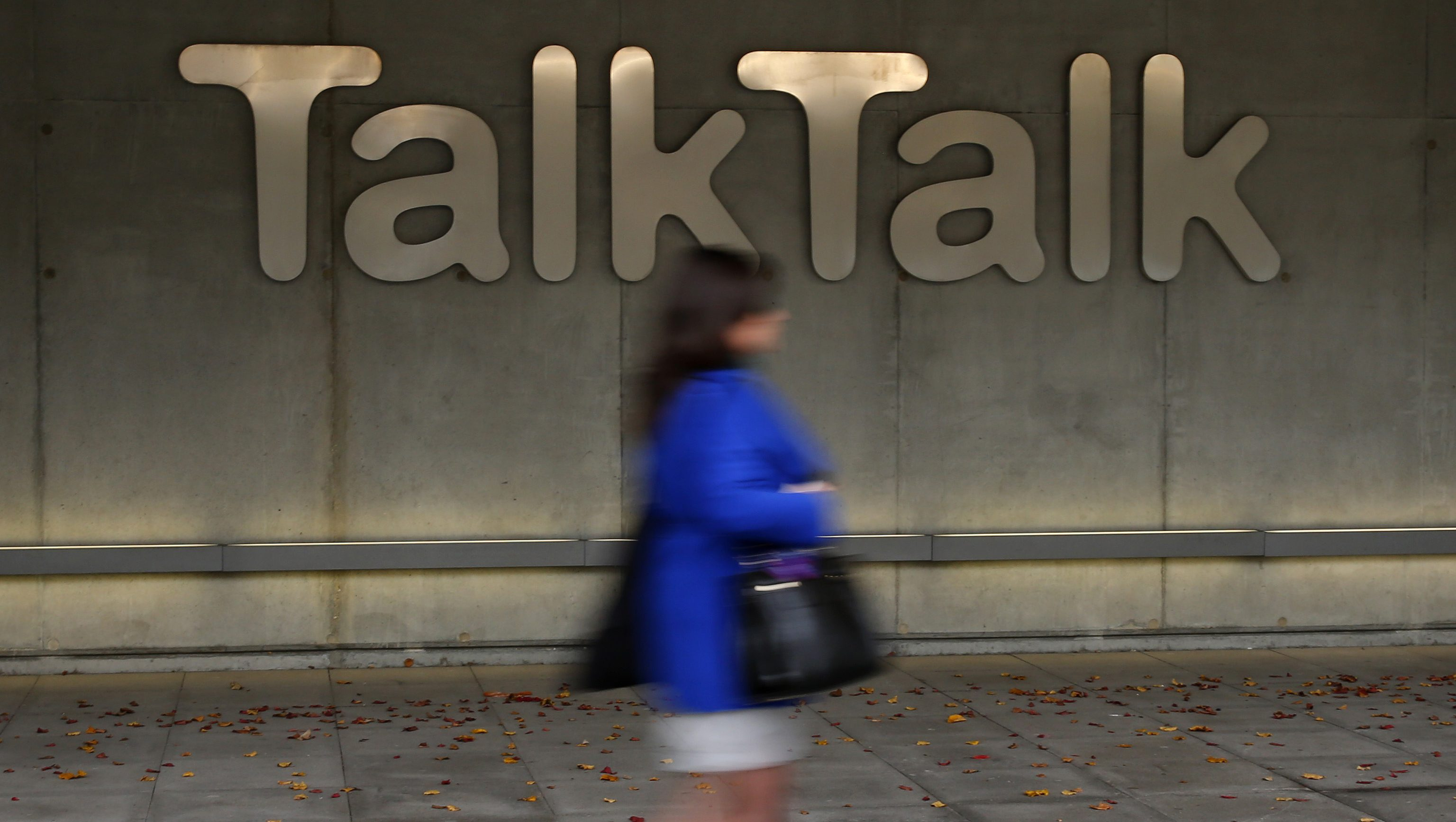 "A woman walks past a company logo outside a TalkTalk building in London, Britain October 23, 2015. Britain's TalkTalk said a ""significant and sustained"" cyber attack on its website could involve the theft of private data from all of the broadband supplier's more than 4 million customers. ""Investigation is ongoing but unfortunately there is a chance that some of the following data has been compromised: names, addresses, date of birth, phone numbers, email addresses, TalkTalk account information, credit card details and/or bank details,"" the company said in a statement late on Thursday. REUTERS/Stefan Wermuth - RTS5RJY"
