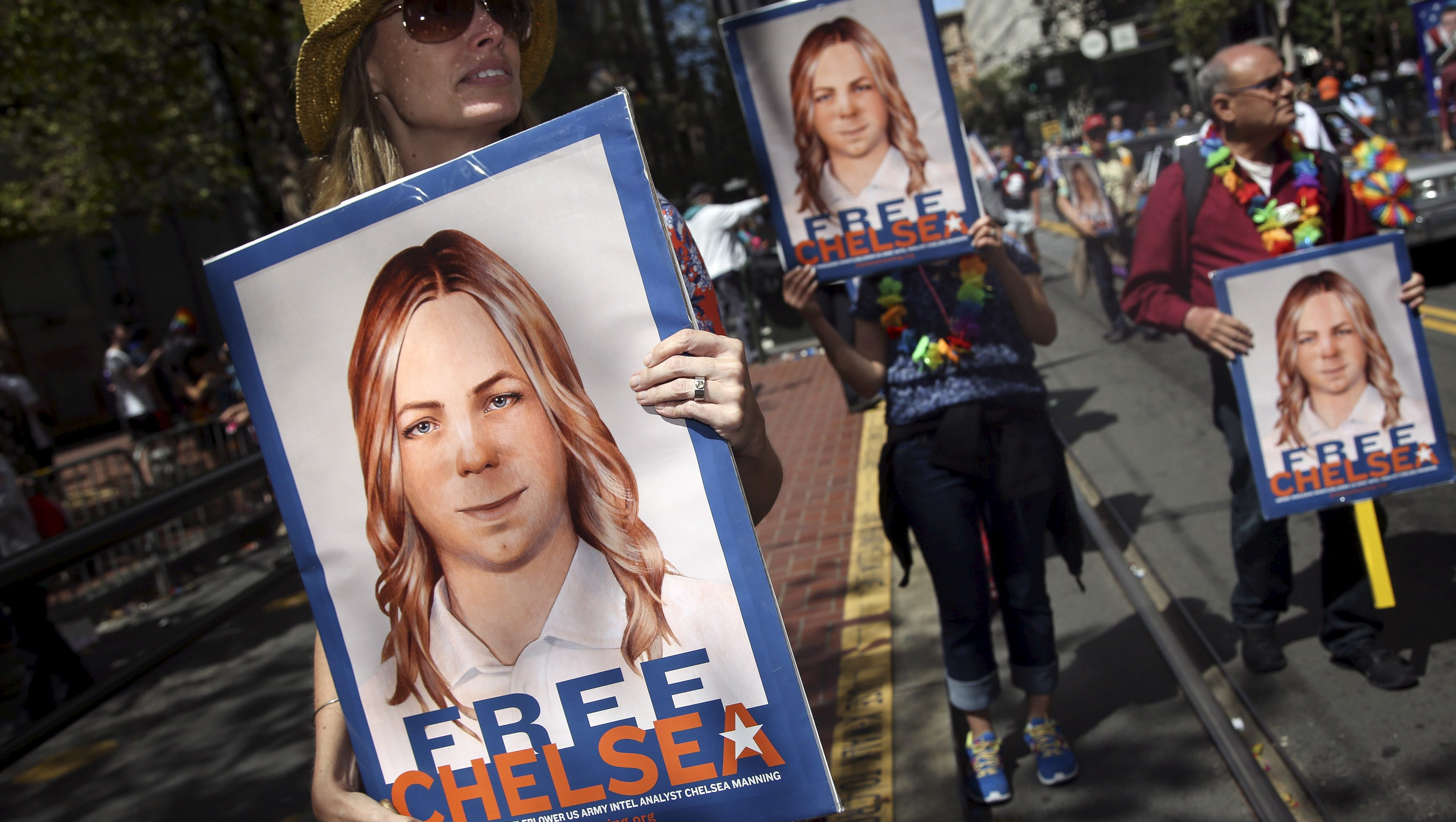 People hold signs calling for the release of imprisoned wikileaks whistleblower Chelsea Manning while marching in a gay pride parade in San Francisco, California June 28, 2015. Manning has appealed to an Army court to overturn her court-martial conviction, a court filing released on Thursday said.  REUTERS/Elijah Nouvelage/File Photo - RTSF29L