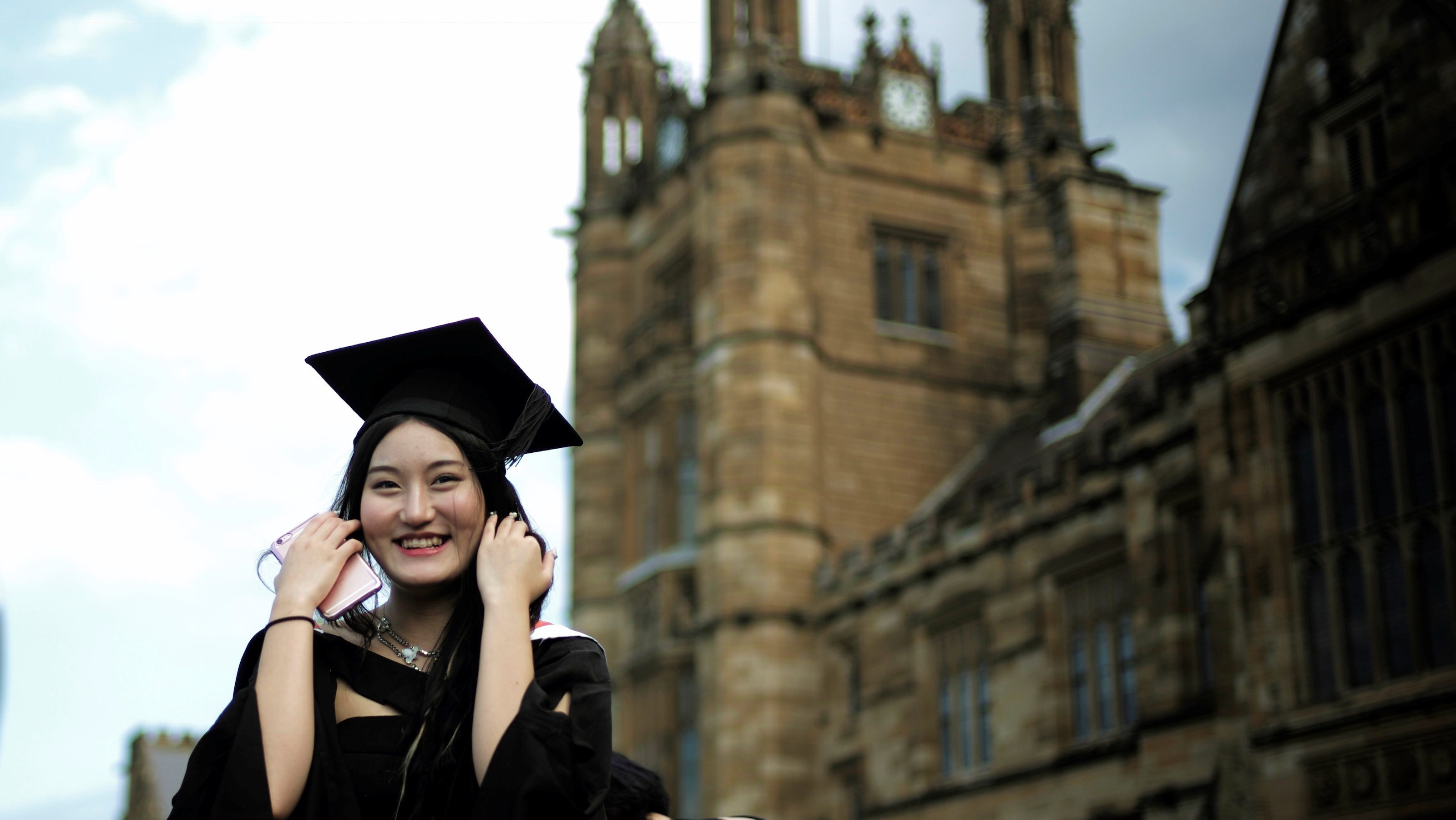 A School of Business graduate poses for a picture taken by a family member (not pictured) outside the main building at the University of Sydney in Australia, April 22, 2016.     REUTERS/Jason Reed                   AUNI - RTSL4VV