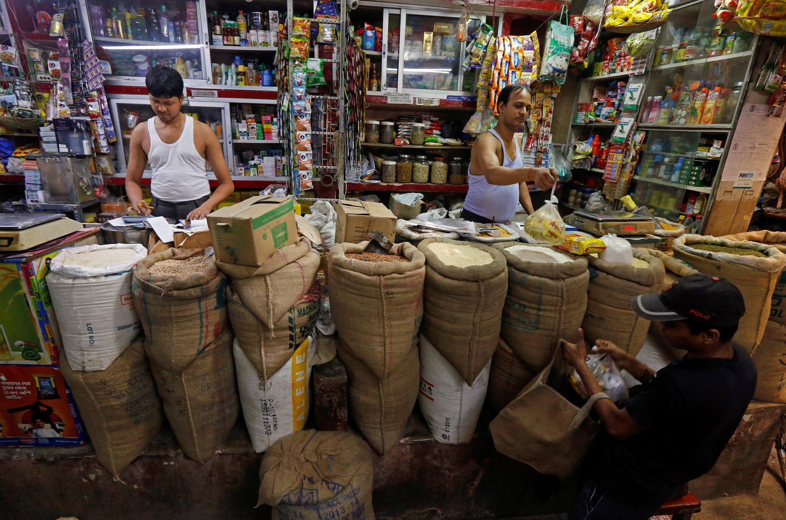 A shopkeeper sells groceries to a customer at his shop in Kolkata, India, September 12, 2016.