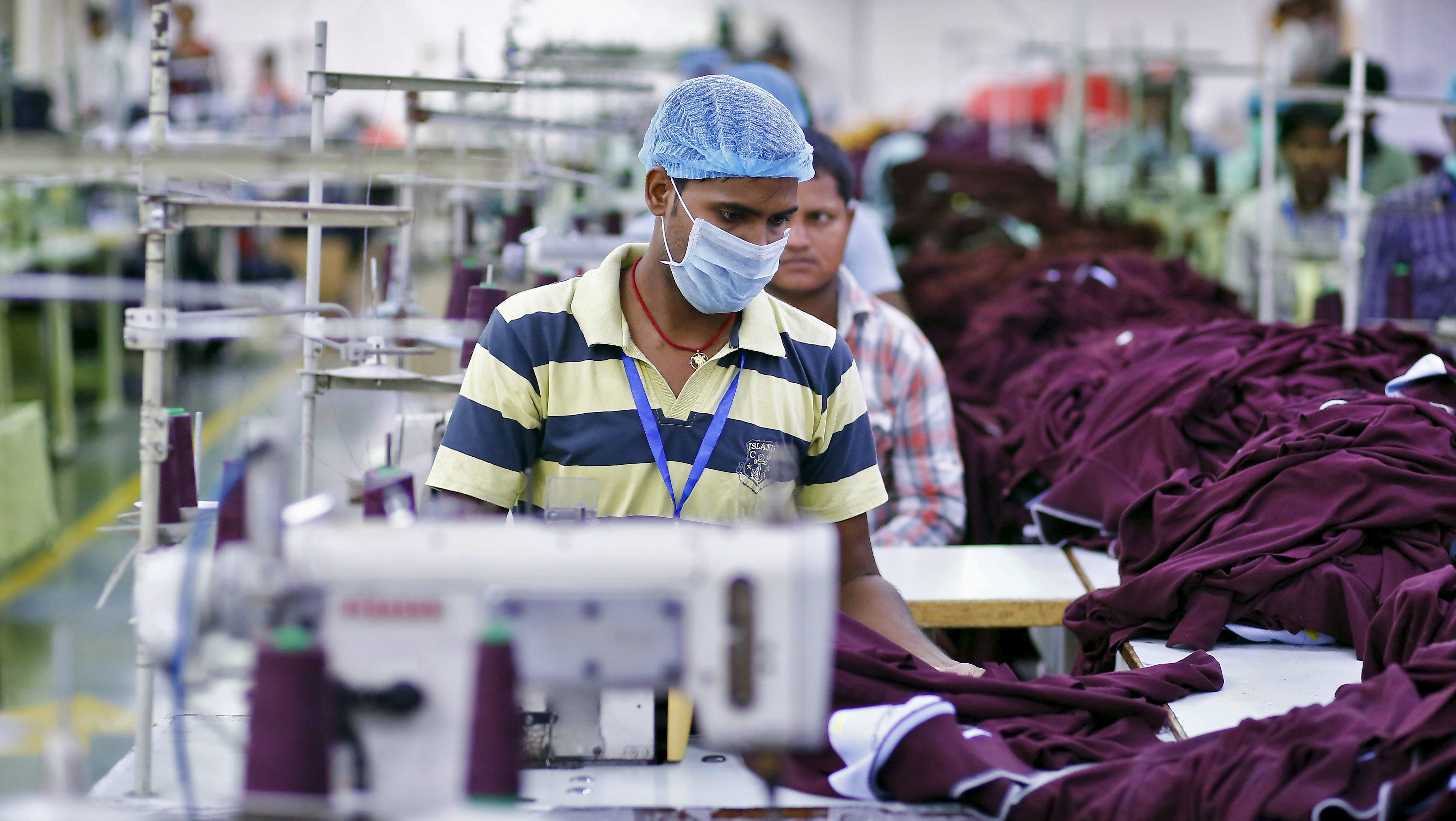 An employee works inside a garment factory of Orient Craft Ltd. in Gurgaon on the outskirts of New Delhi, India, July 3, 2015. To match Insight INDIA-LABOUR/REFORMS Picture taken July 3, 2015. REUTERS/Anindito Mukherjee - RTX1LTLA