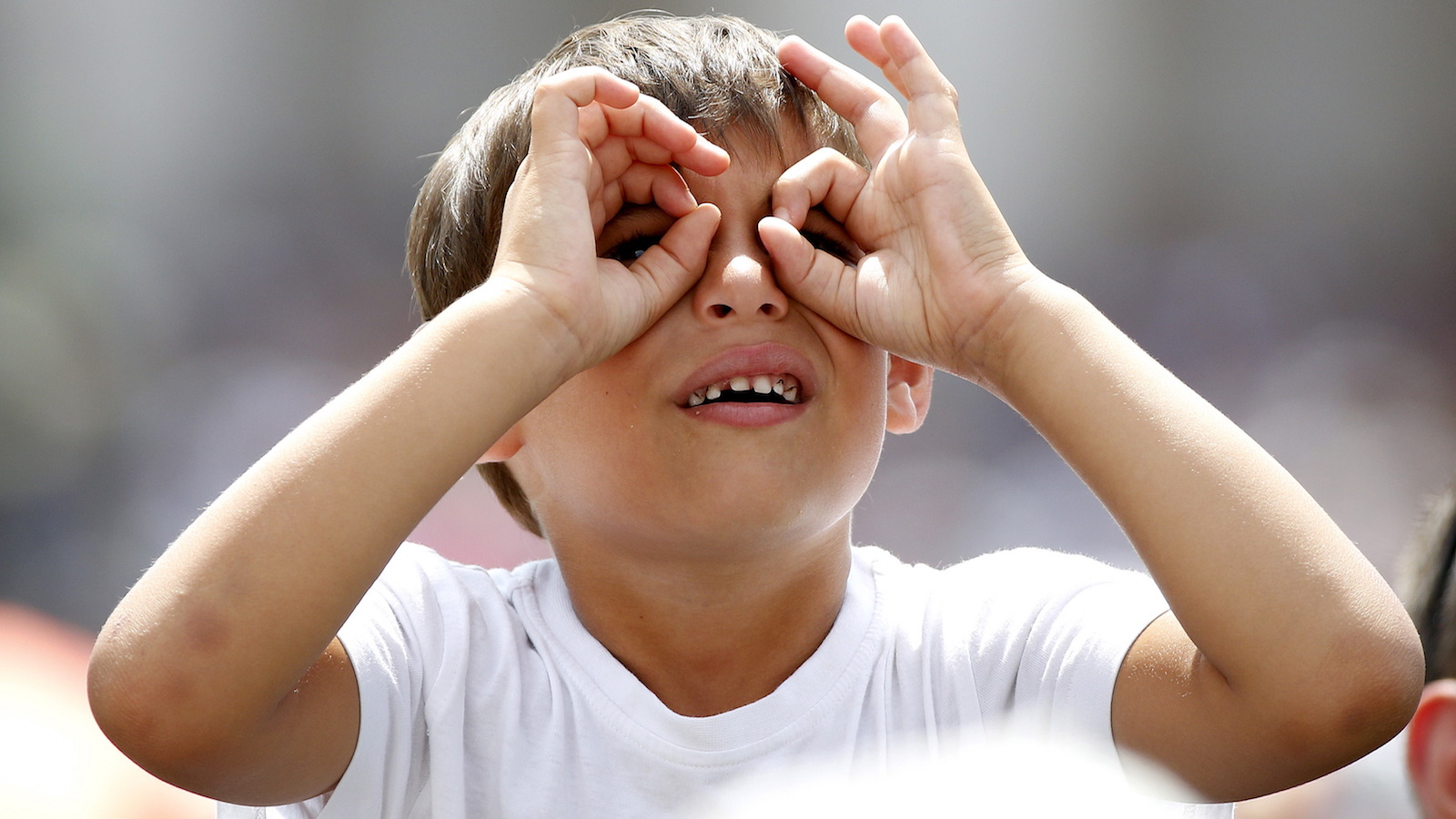 A child imitates using a pair of binoculars as Pope Francis leads the Angelus prayer in Saint Peter's Square at the Vatican