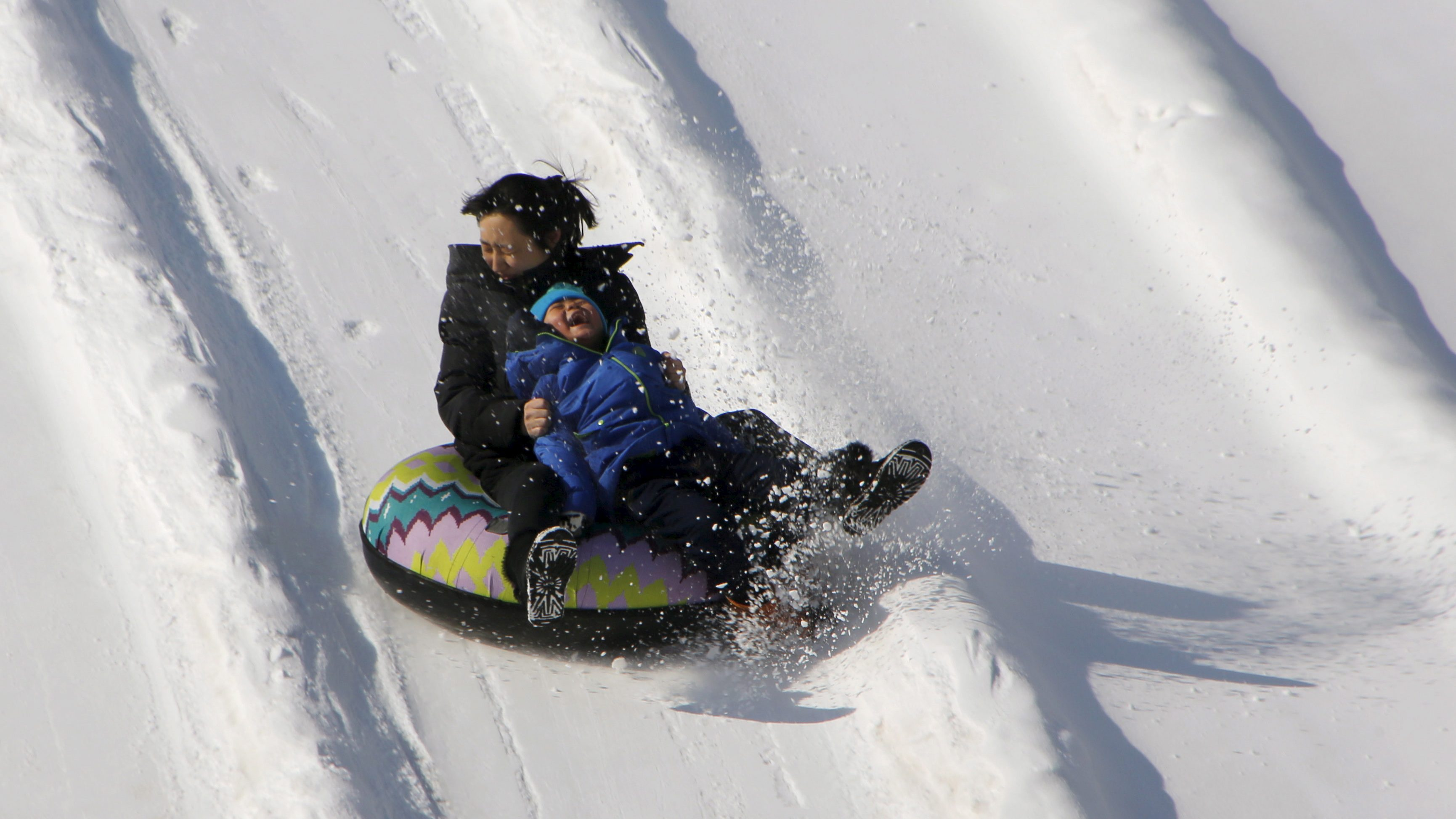 A woman and a boy on a tube ride a slide covered with snow during the Ice and Snow carnival at Taoranting park in Beijing, China, January 25, 2016.