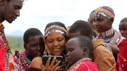 Maasai girls and a man watch a video on a mobile phone prior to the start of a social event advocating against harmful practices such as Female Genital Mutilation (FGM) at the Imbirikani Girls High School in Imbirikani, Kenya, April 21, 2016.