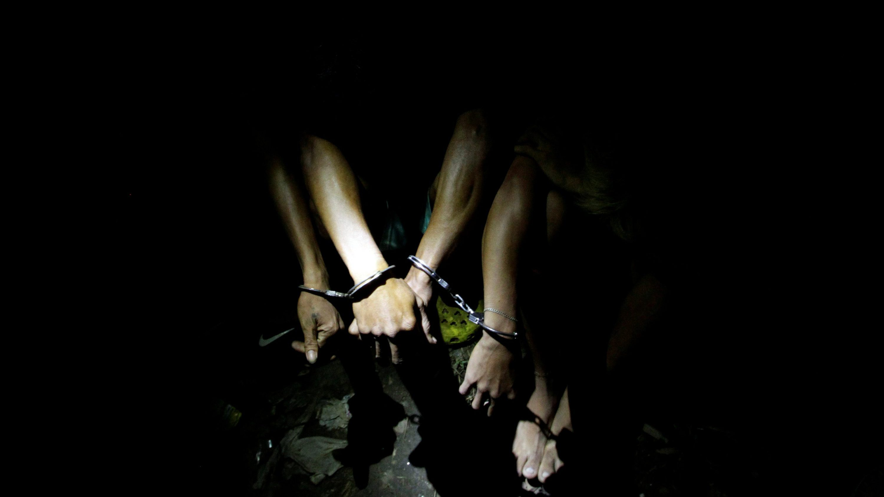 Men are handcuffed after they were detained by police during a police anti-illegal drugs operation in Quezon city, Metro Manila, Philippines November 9, 2016. Picture taken November 9, 2016.