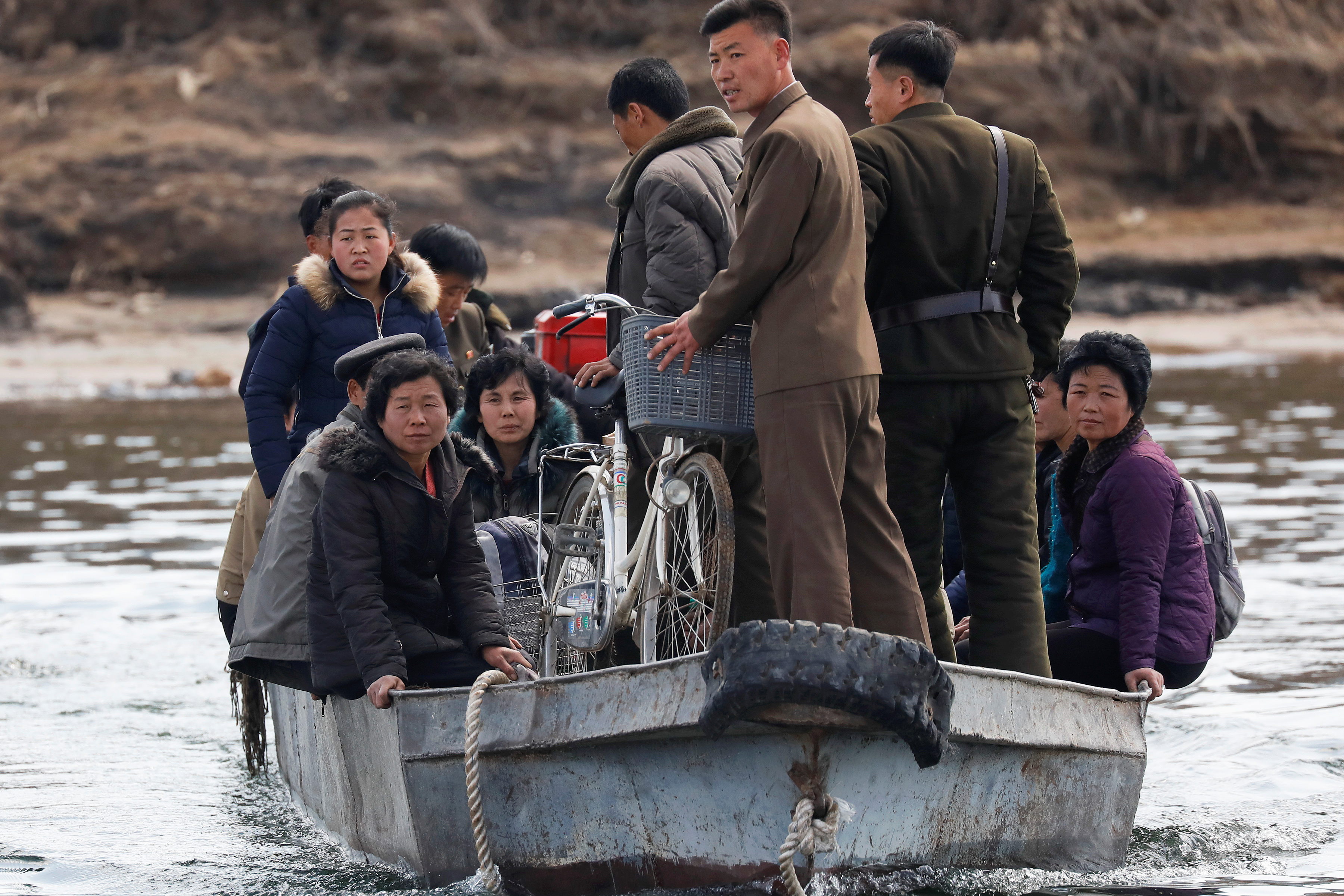 People are transported on a boat from the North Korean side of the Yalu River to an island north of the town of Sinuiju, North Korea, April 1, 2017.