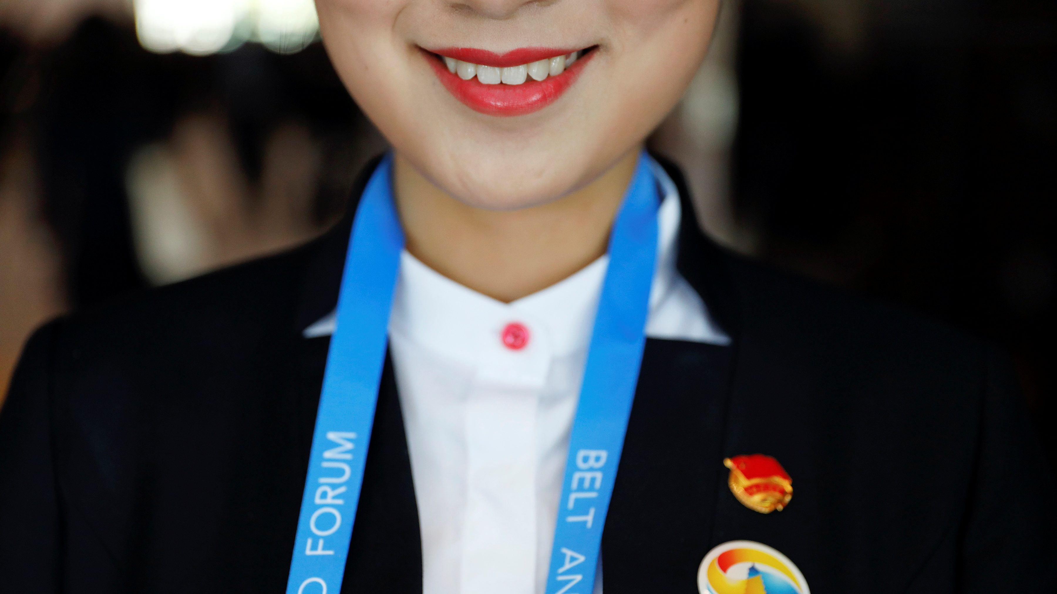A volunteer member of staff smiles as delegates arrive to the venue of the Belt and Road Forum in Beijing