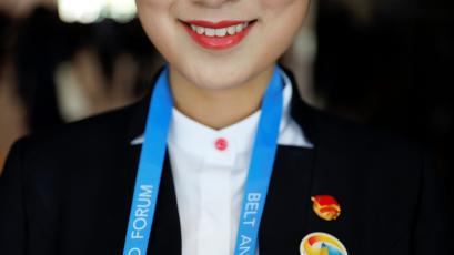 A volunteer member of staff smiles as delegates arrive to the venue of the Belt and Road Forum in Beijing, China, May 14, 2017.