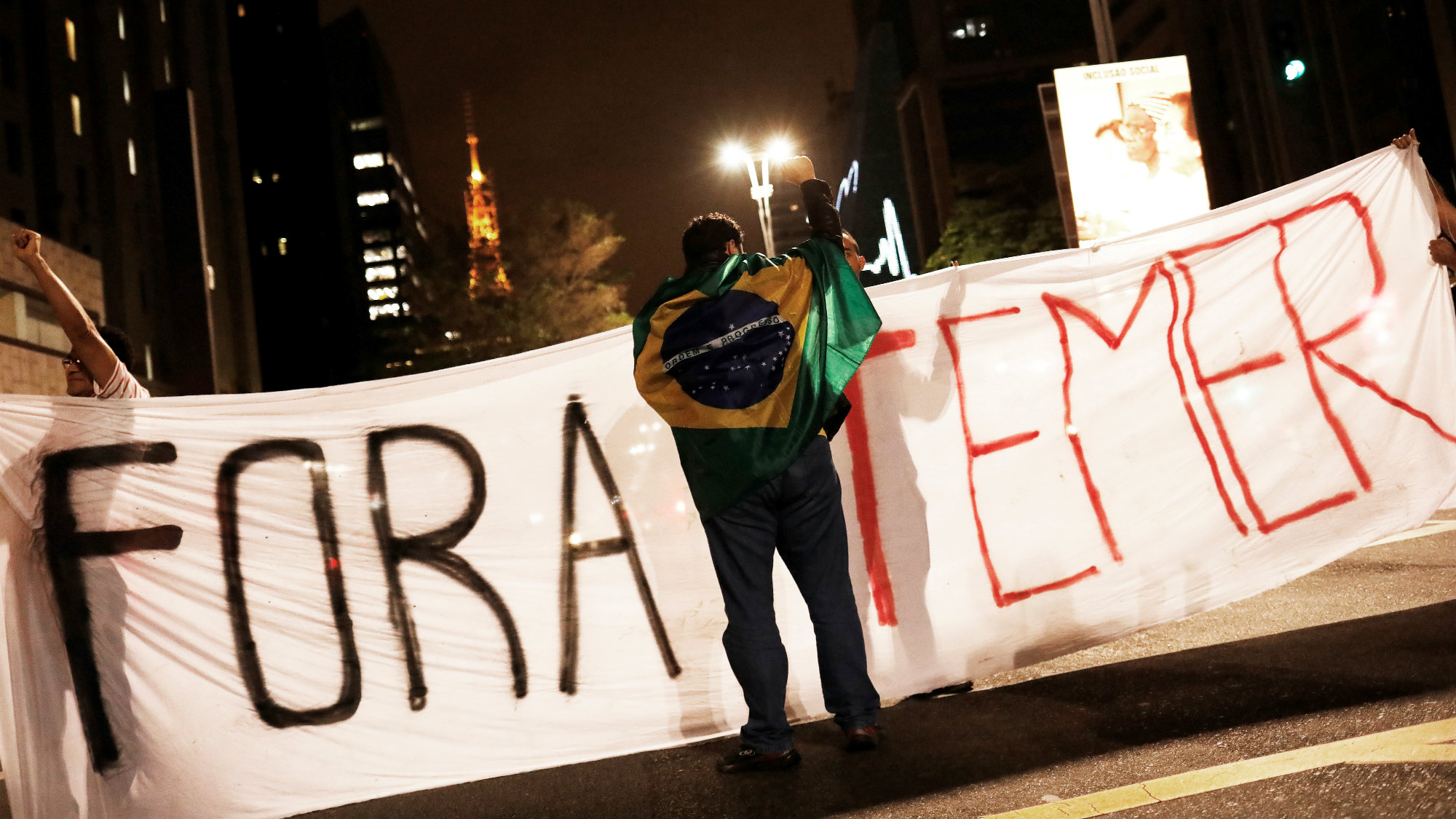 """A demonstrator draped with a Brazilian Flag is pictured in front a banner reading """"Temer out"""" during a protest against Brazil's President Michel Temer in Sao Paulo, Brazil"""