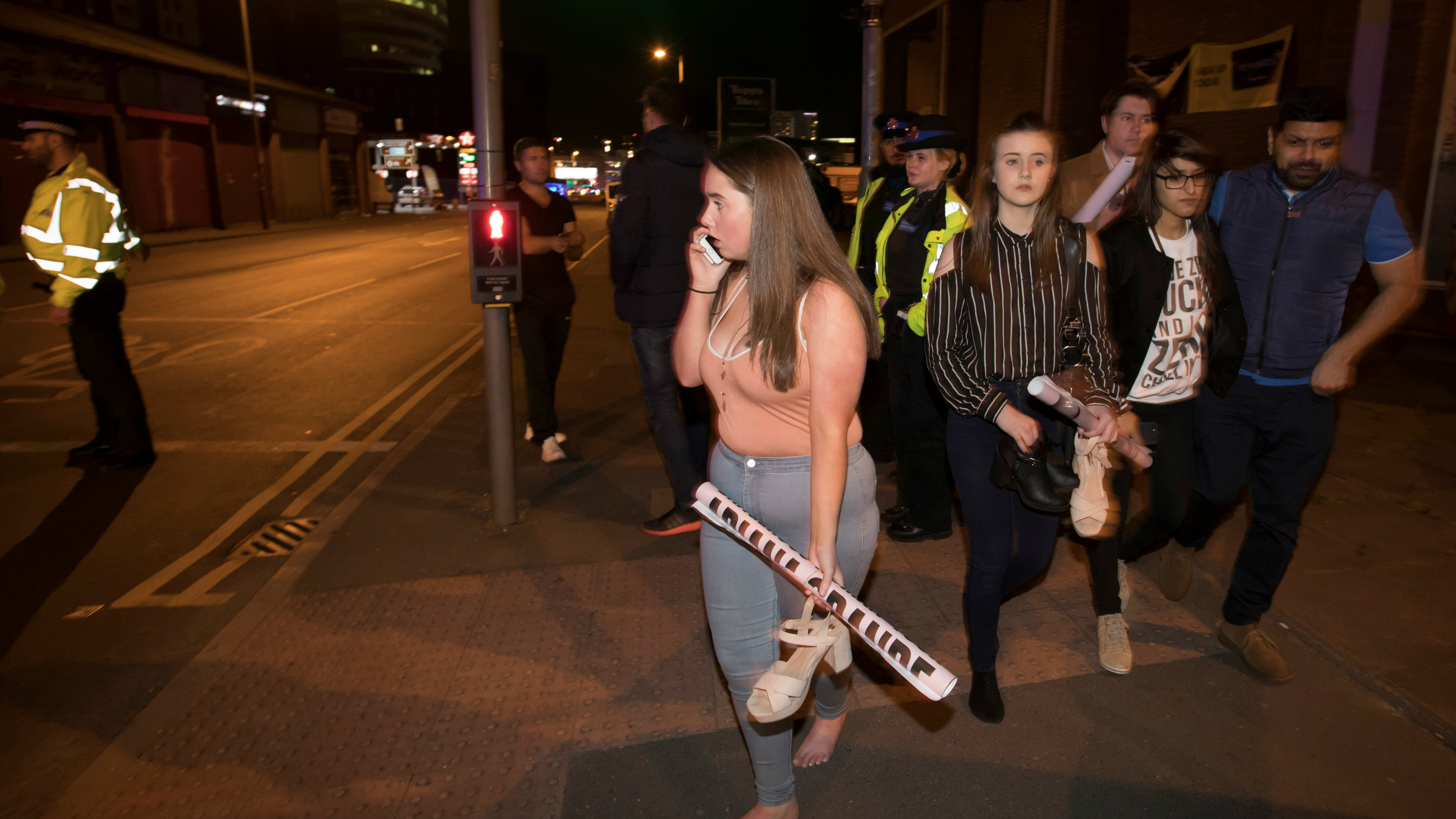 Concert goers react after fleeing the Manchester Arena in northern England where U.S. singer Ariana Grande..