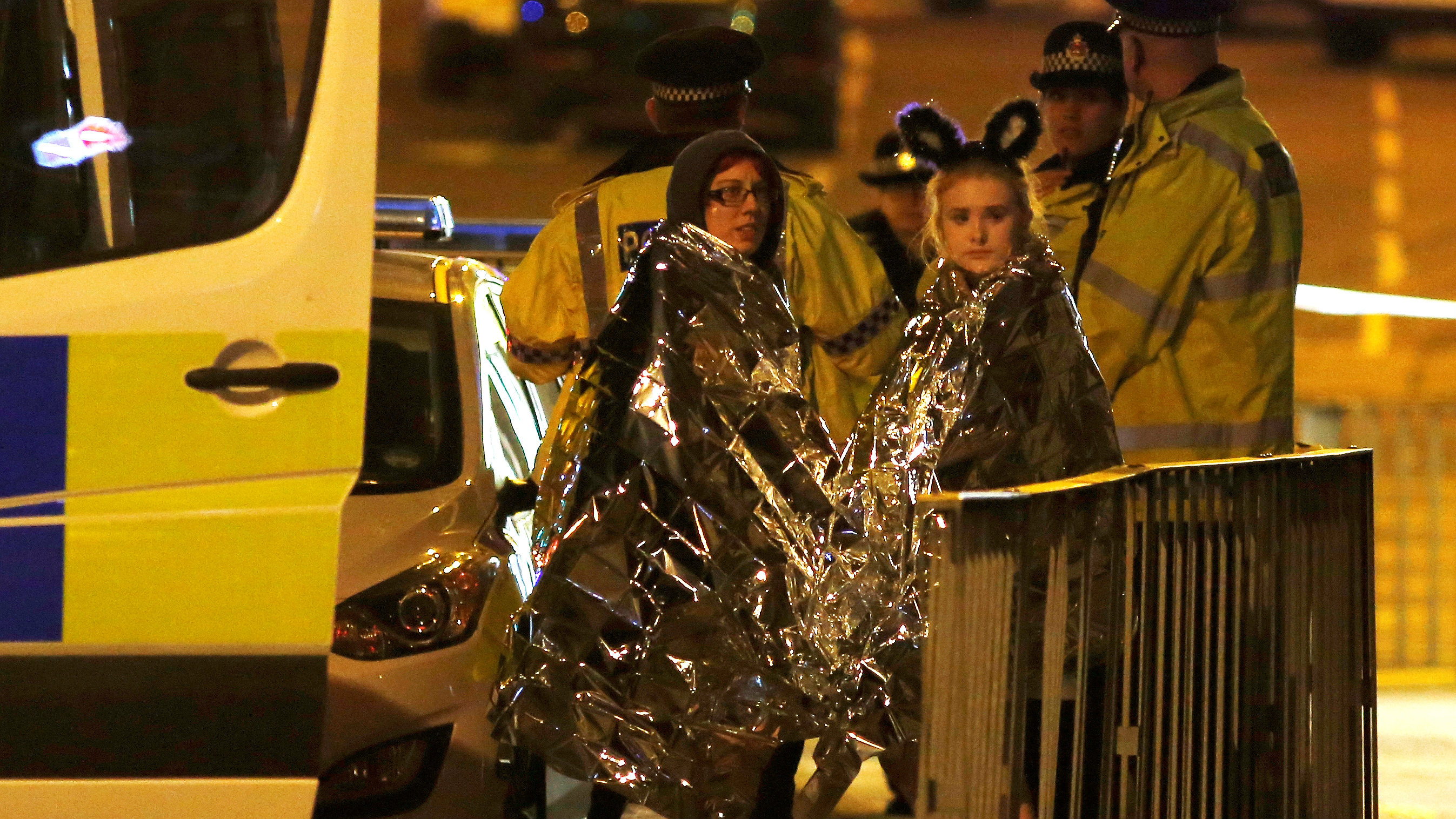 Two women wrapped in thermal blankets stand near the Manchester Arena following a terror attack on May 22