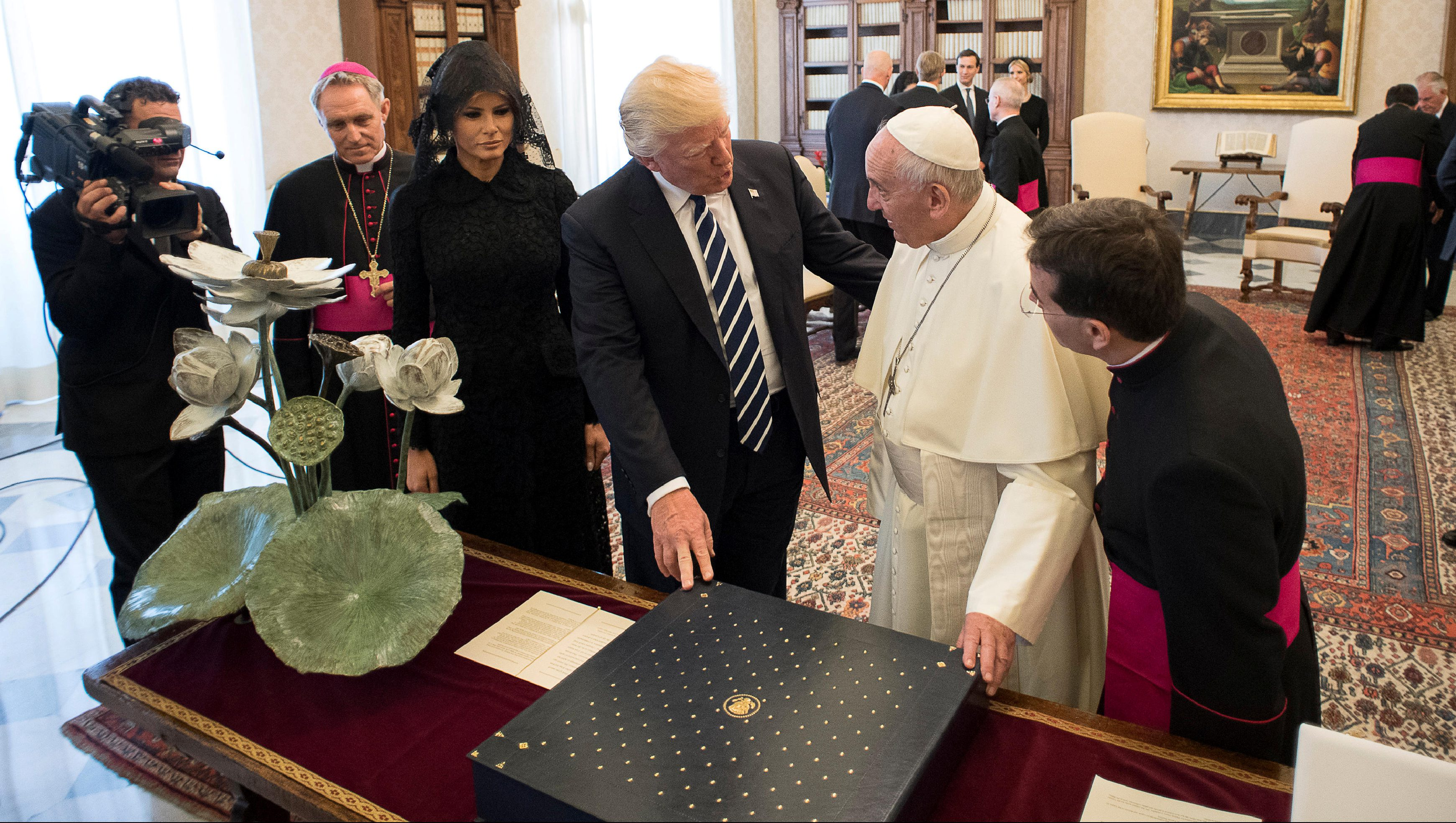 Pope Francis exchanges gifts with U.S. President Donald Trump and his wife Melania during a private audience at the Vatican