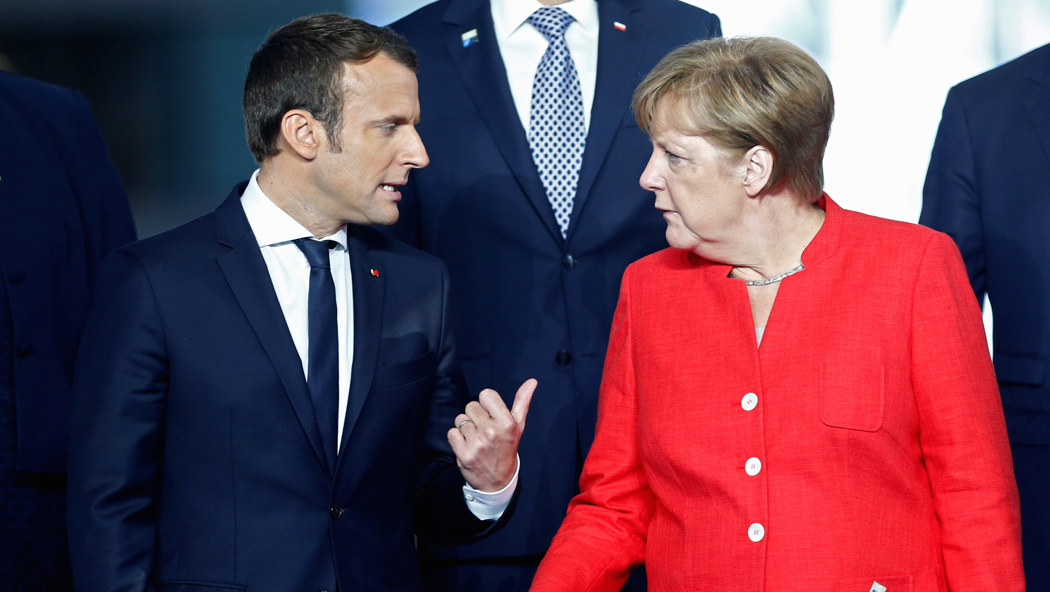 French President Emmanuel Macron (L) and  German Chancellor Angela Merkel (R) speak as they gather with NATO member leaders before the start of their summit in Brussels, Belgium, May 25, 2017.