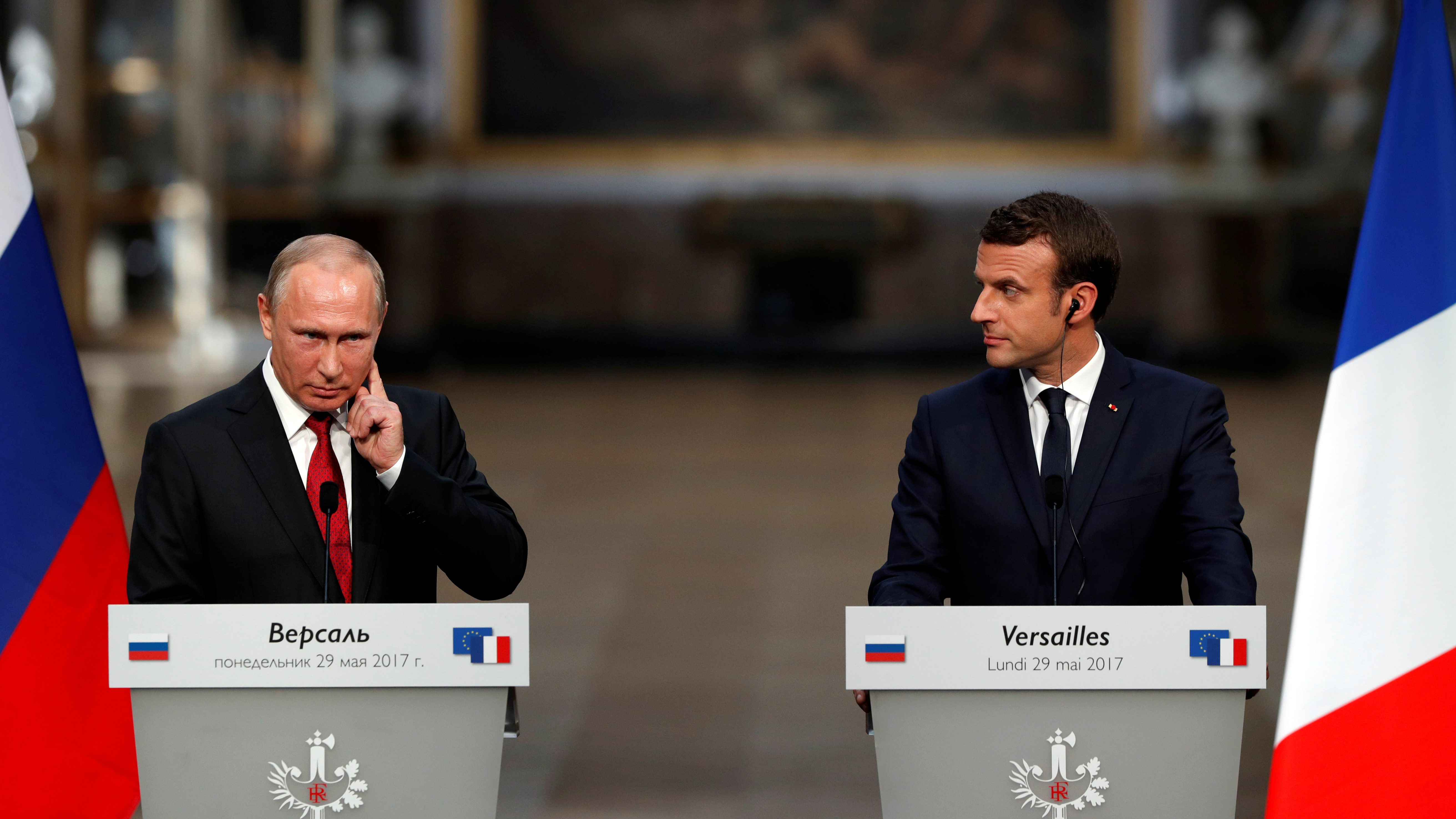 French President Emmanuel Macron (R) and Russian President Vladimir Putin (L) react during a joint press conference at the Chateau de Versailles before the opening of an exhibition marking 300 years of diplomatic ties between the two countries in Versailles, France, May 29, 2017.   REUTERS/Philippe Wojazer - RTX38490