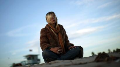 A woman meditates at sunset on Venice Beach in Los Angeles, California