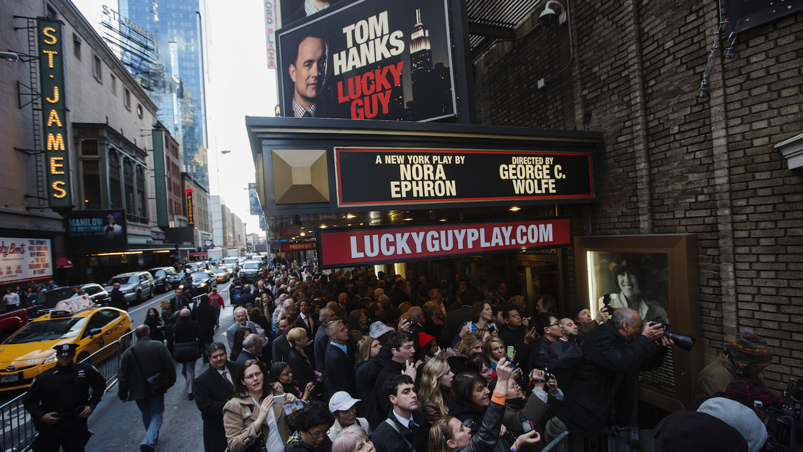 Fans line up outside Broadhurst Theater to watch movie stars arrive for the premiere of the play Lucky Guy in New York
