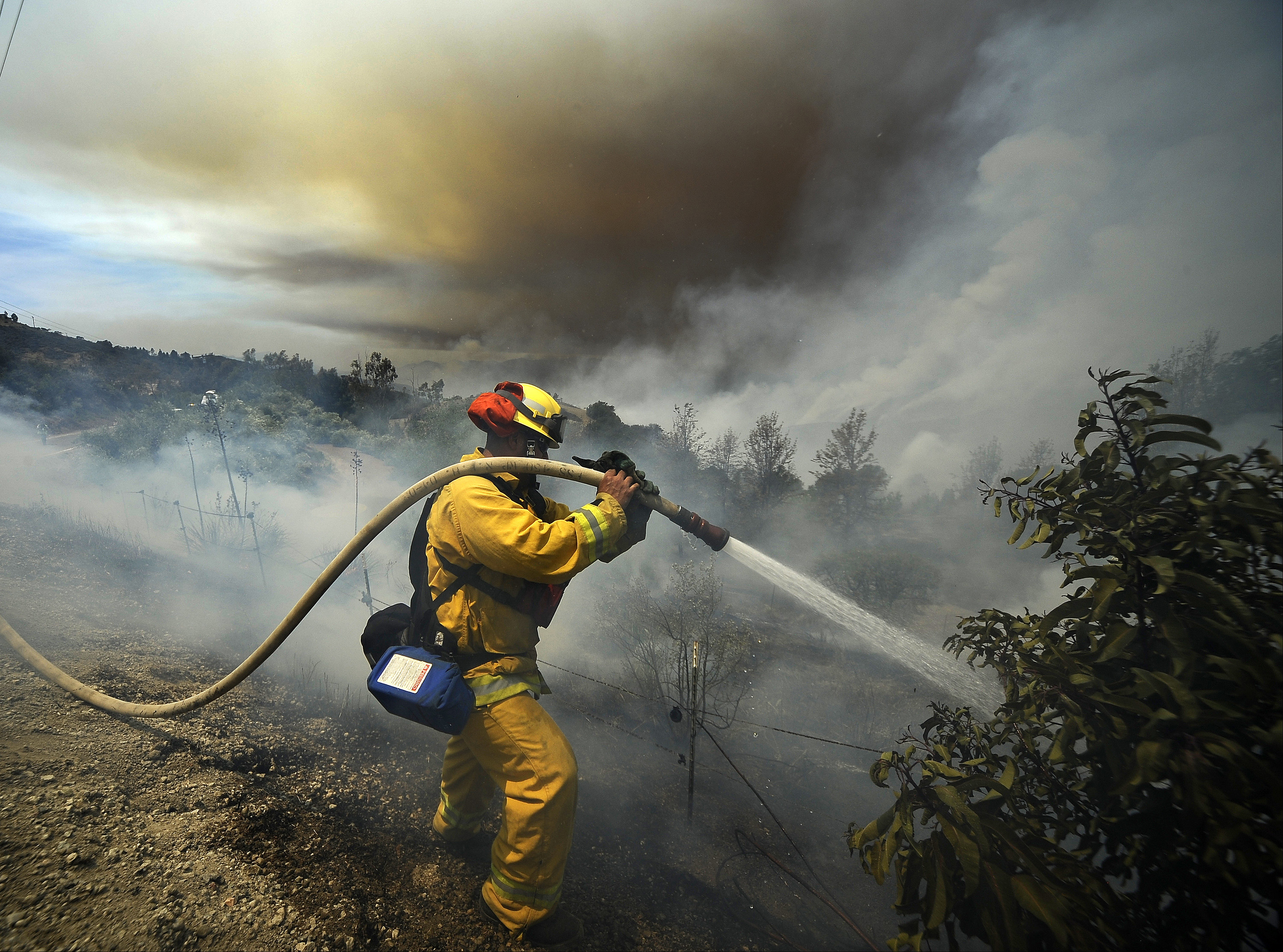 Firefighters battle fire during the second day of the Springs Fire in the mountain areas of Ventura County, California May 3, 2013. A fierce, wind-whipped wildfire spread on Friday along the California coast northwest of Los Angeles, threatening several thousand homes and a military base as more than 1,100 dwellings were ordered evacuated and a university campus was closed.
