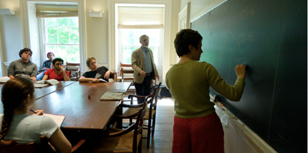 A student writes on a chalk board inside of a St John's College classroom
