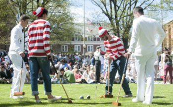 Students dressed in all white compete against students dressed in Where's Waldo garb in a competitive game of croquet at St John's College