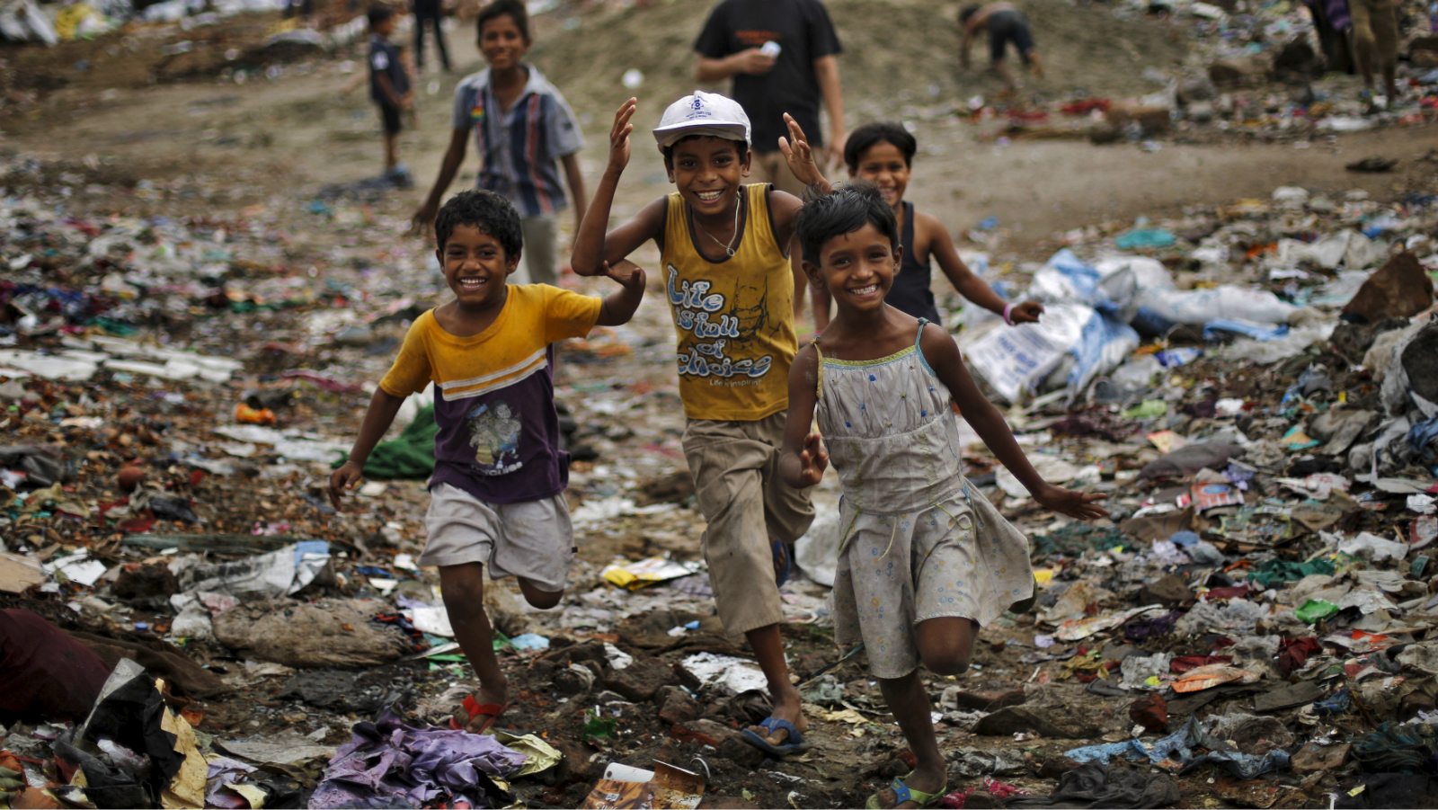 Children react to the camera as they play outside their homes in New Delhi, India May 13, 2015.