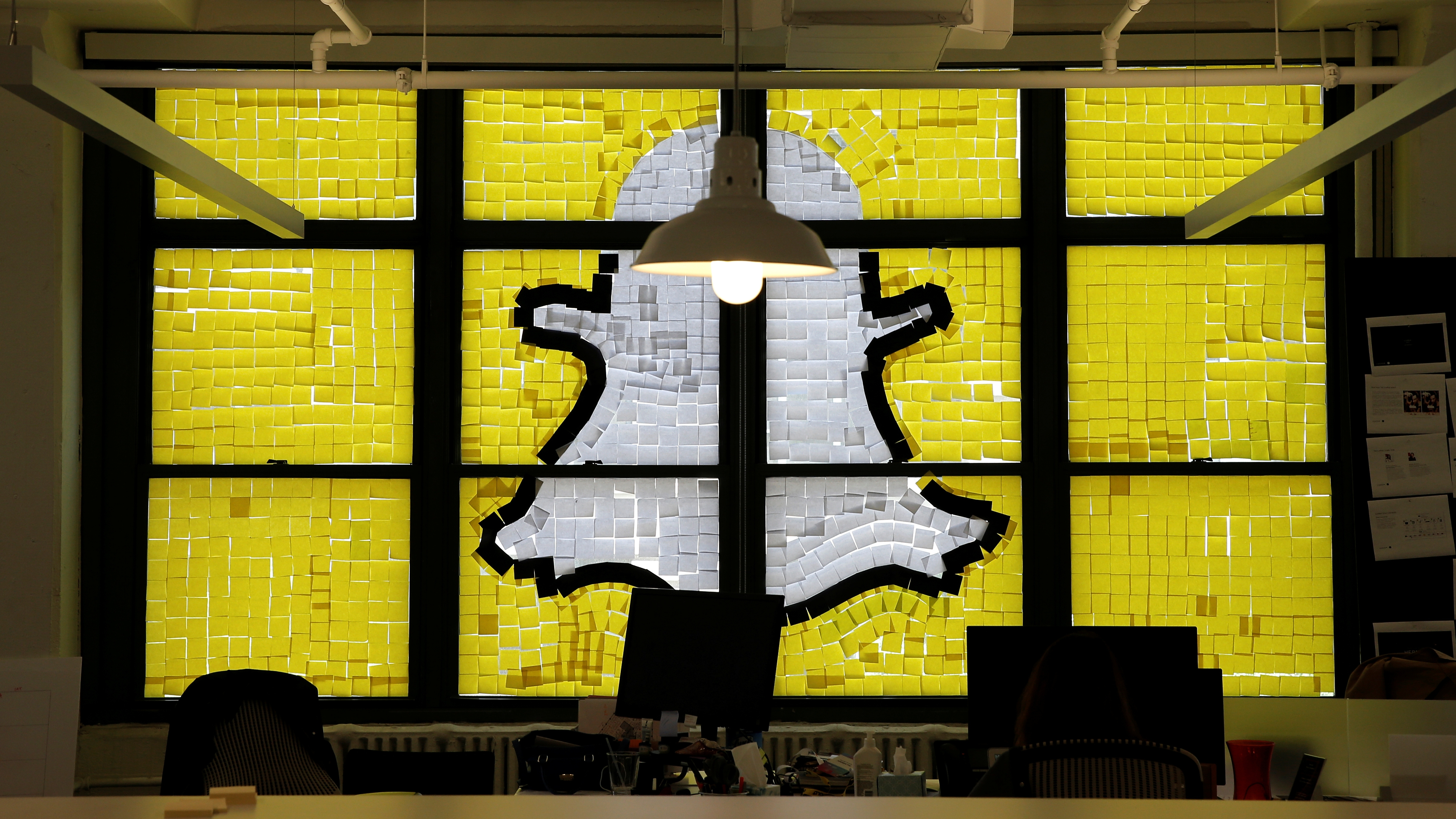 "An image of the Snapchat logo created with Post-it notes is seen in the windows of Havas Worldwide at 200 Hudson Street in lower Manhattan, New York, U.S., May 18, 2016, where advertising agencies and other companies have started what is being called a ""Post-it note war"" with employees creating colorful images in their windows with Post-it notes. REUTERS/Mike Segar"