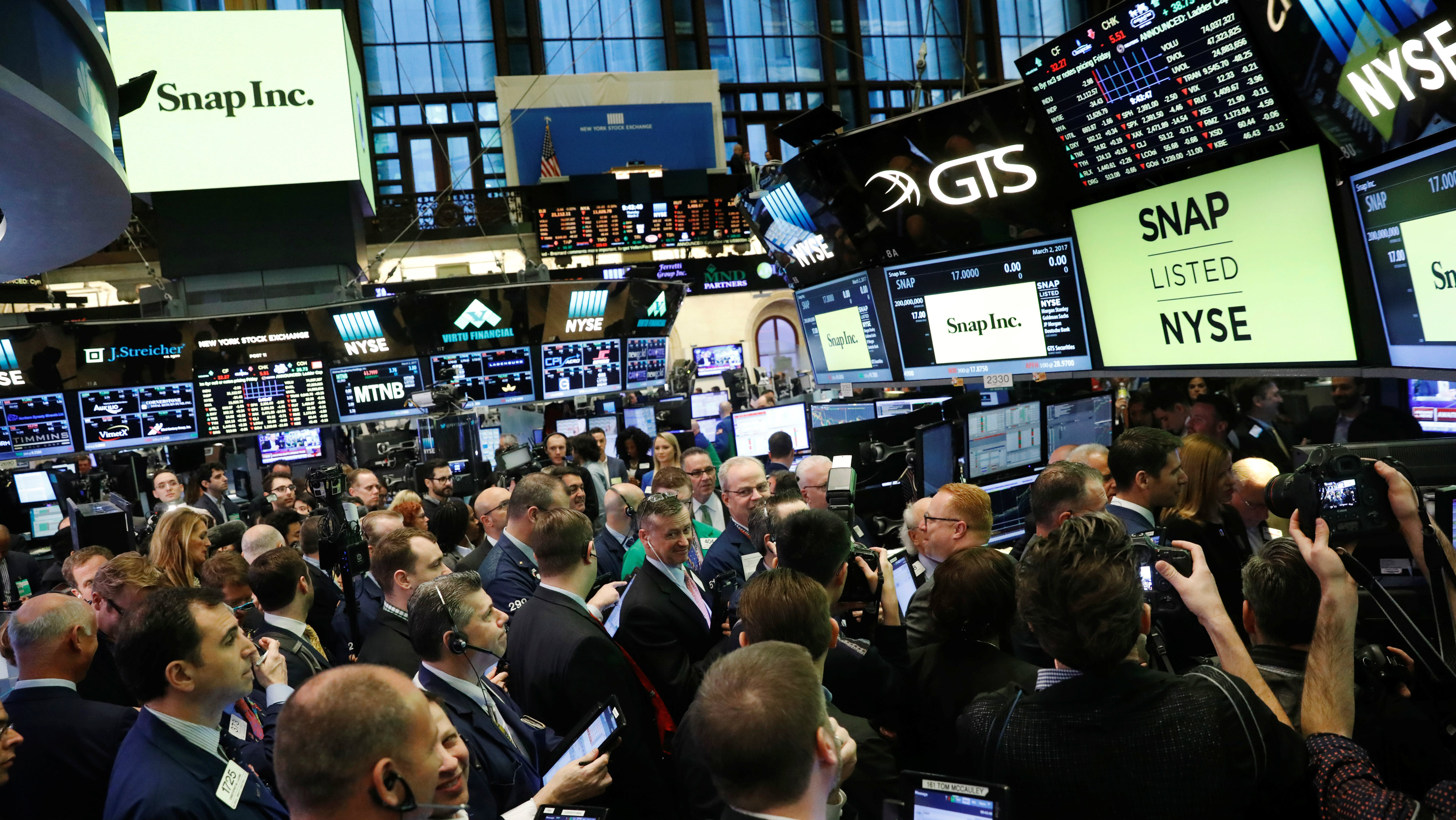Traders on the floor of the New York Stock Exchange (NYSE) wait for Snap Inc to post their IPO