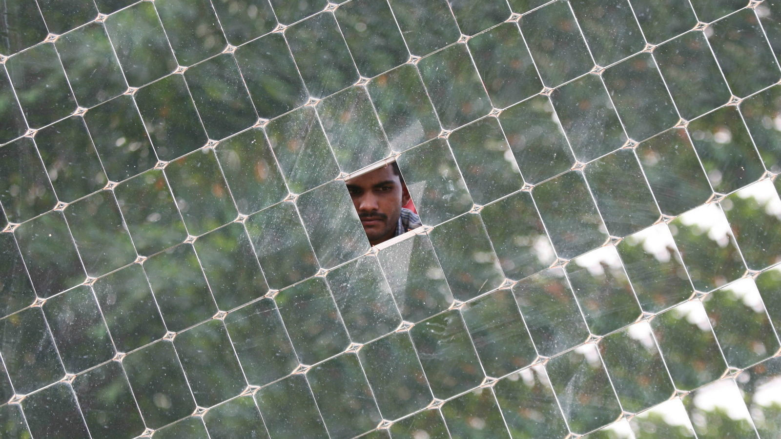 A worker looks through a solar concentrator panel (solar parabolic dish) at the Gadhia solar energy systems manufacturing unit at Gundlav village, about 400 km (250 miles) south of the western Indian city of Ahmedabad, December 16, 2009.