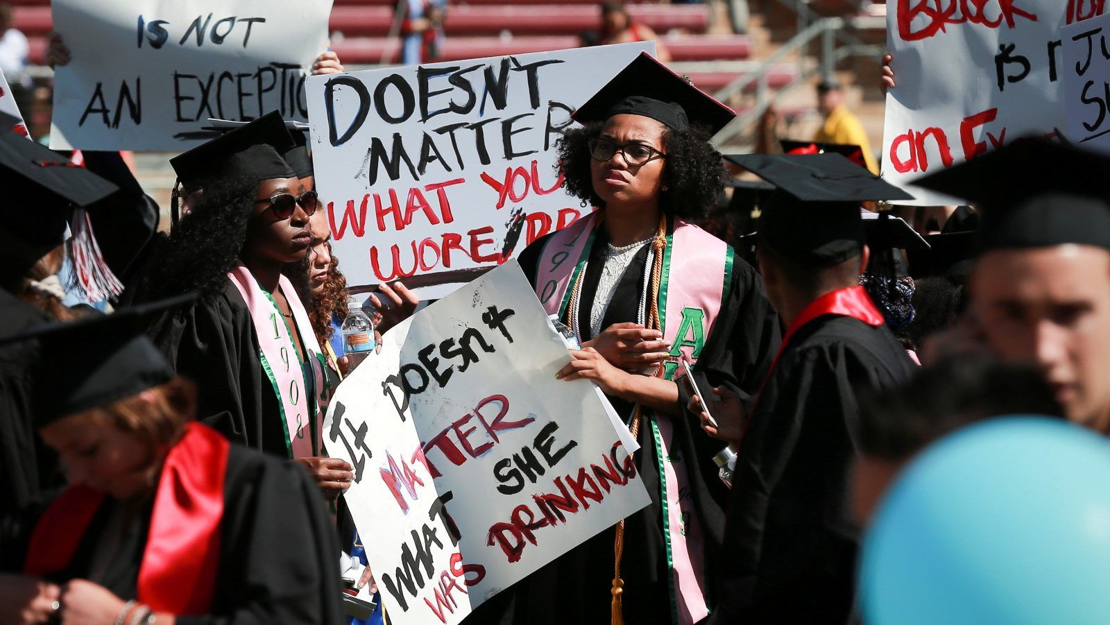 Protesters hold signs to raise awareness of sexual assault on campus in the wake of the national attention brought by the Stanford rape case at the Stanford University commencement ceremony in Palo Alto, California, U.S. June 12, 2016. The case made national headlines after the judge handed down what many considered to be a particularly light sentence. REUTERS/Elijah Nouvelage - RTX2FTG7