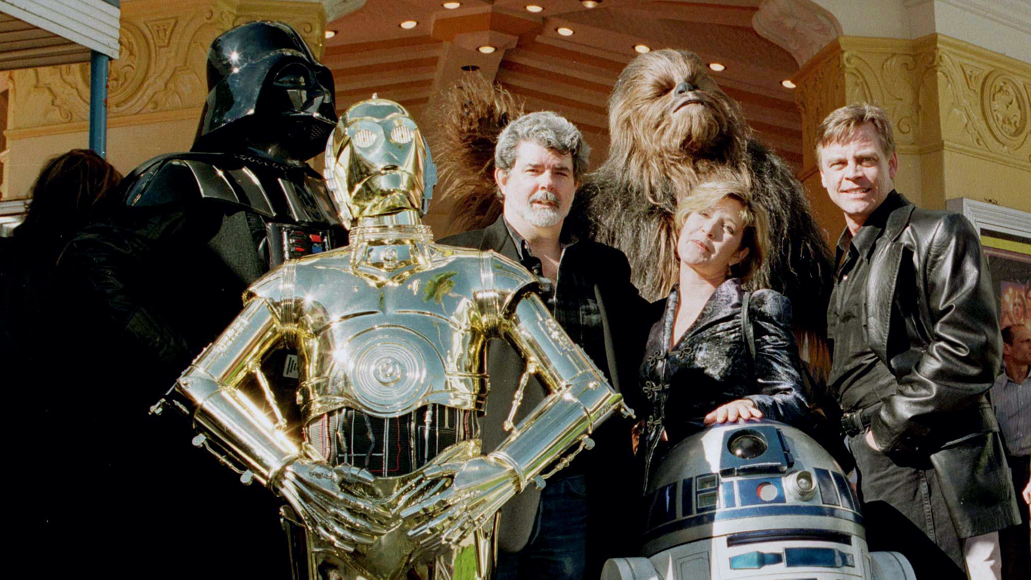 """Director and writer of """"Star Wars"""" George Lucas (C) poses with cast members Carrie Fisher and Mark Hamill along with characters """"Darth Vader"""" (L) """"3CPO"""" (in gold) """"R2D2"""" (short robot) and """"Chewbacca"""" (background) during the premiere of """"Star Wars Special Editon"""" in Los Angeles January 18. The film is celebrating its 20th anniversary. - RTXHQDM"""