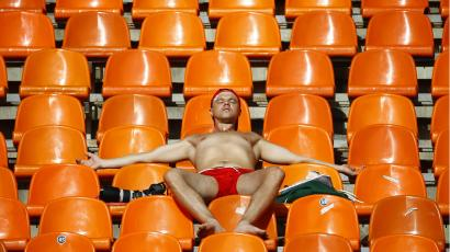 A shirtless man in red shorts sprawls out on orange chairs in a stadium to get a tan.