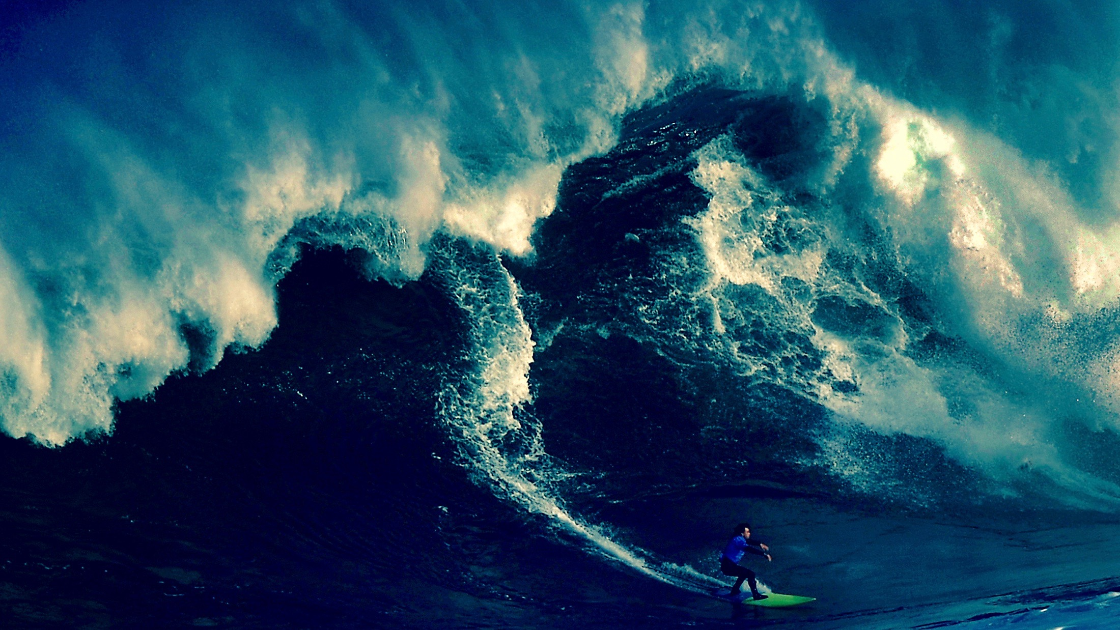 A surfer rides a large wave.
