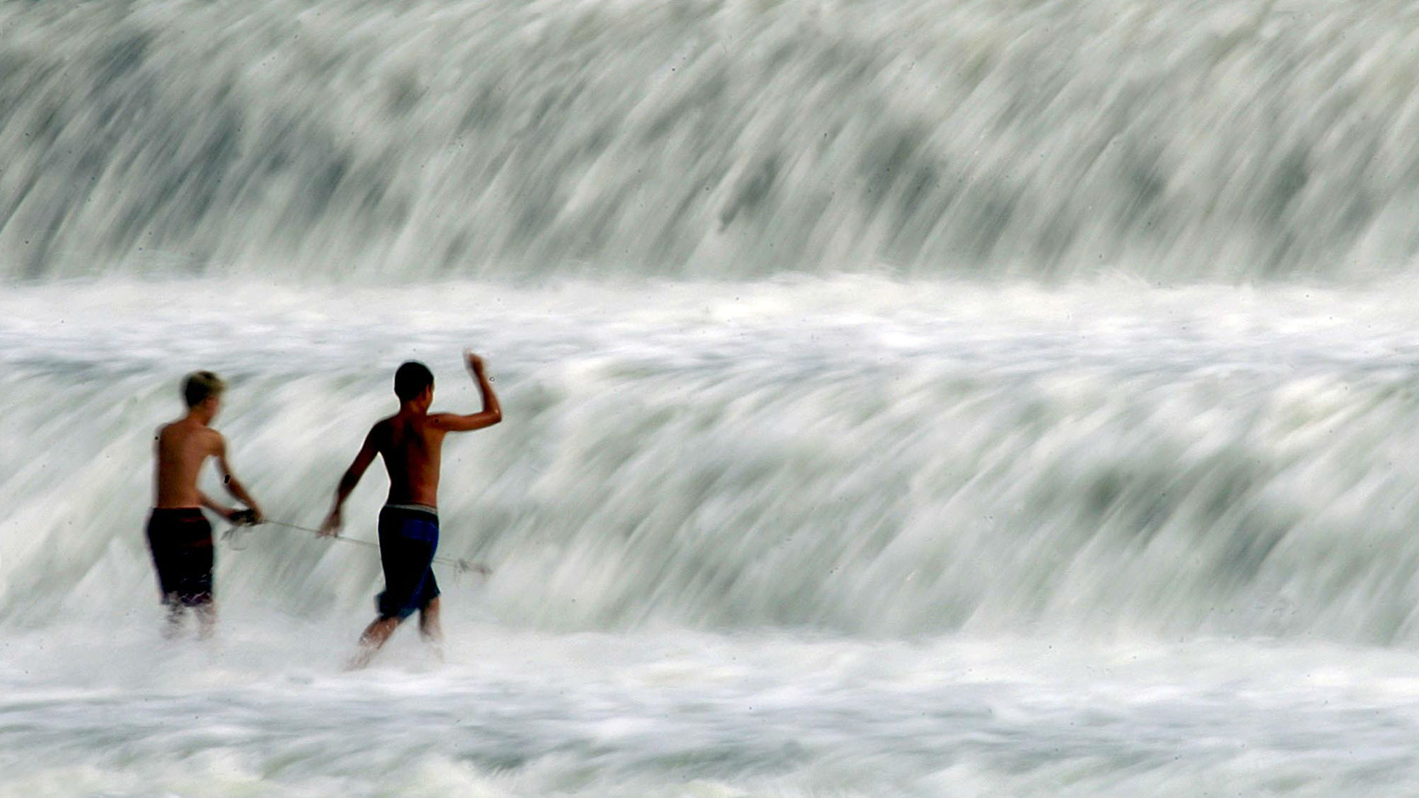 """Two boys play in a waterfall of the Lech river, called """"Lech falls"""", in the south Bavarian town of Landsberg, about 50 km west of Munich August 26, 2003. Mild summer weather has warmed southern Germany with temperatures around 25-30 degrees Celsius."""