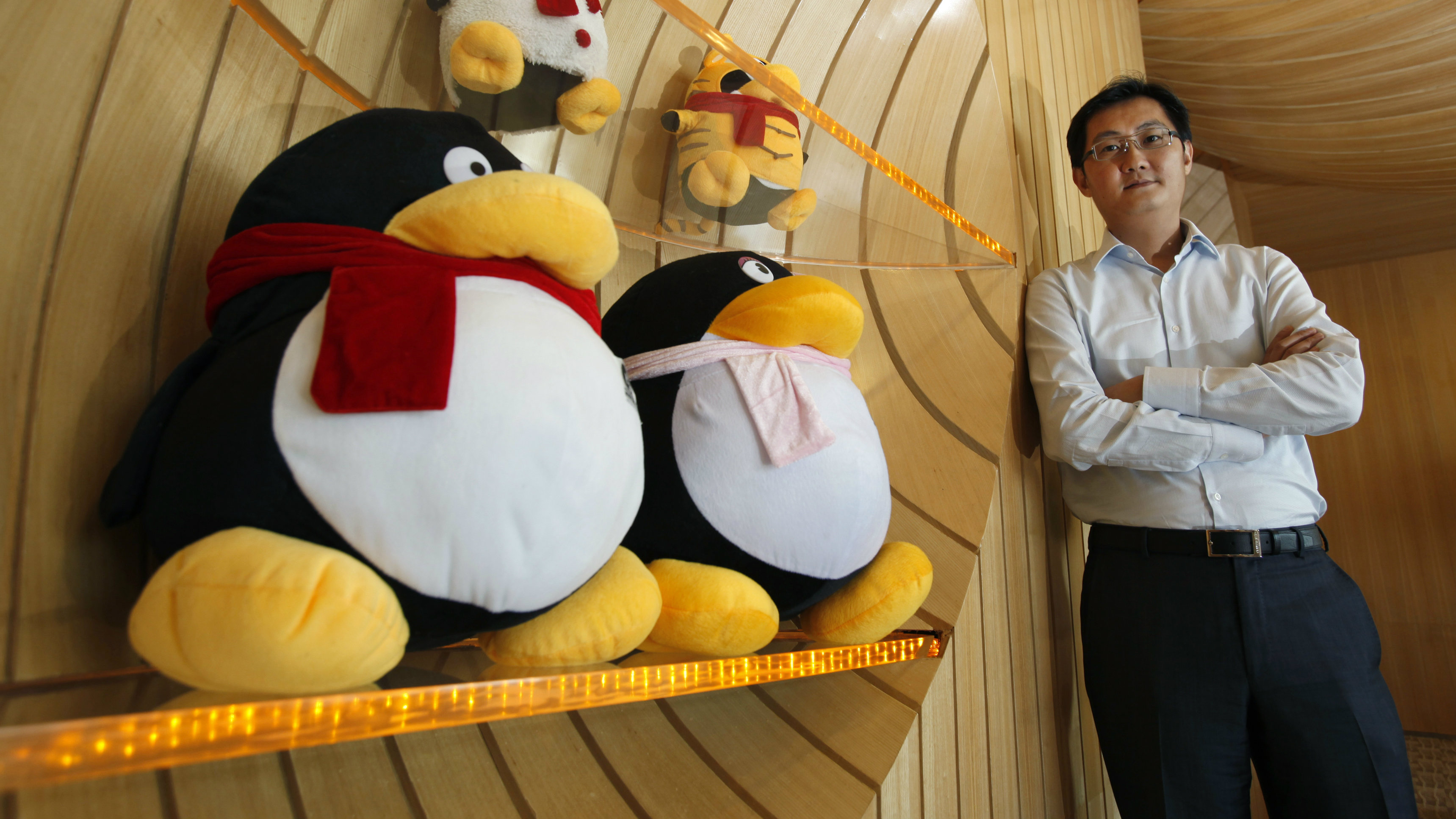 Tencent Chairman and CEO Pony Ma poses with mascots for QQ.com inside the company's headquarters in Nanshan Hi-Tech Industrial Park in the southern Chinese city of Shenzhen during an interview by Reuters June 9, 2011.
