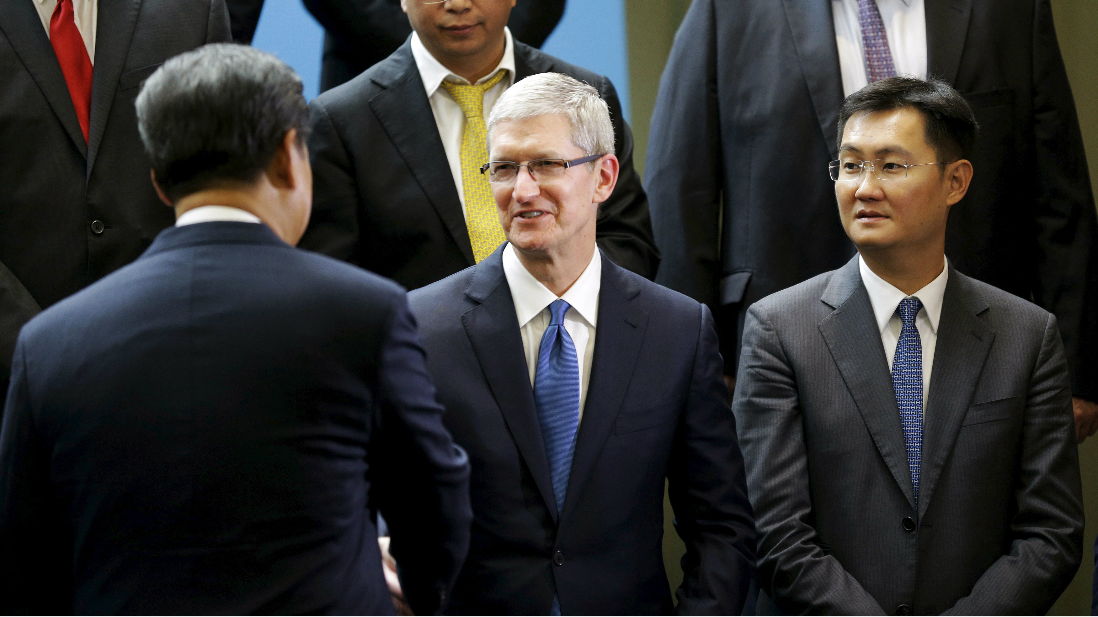 Chinese President Xi Jinping (L) shakes hands with Apple Inc. CEO Tim Cook (C), as Tencent CEO Pony Ma (R) looks on, during a gathering of CEOs and other executives at Microsoft's main campus