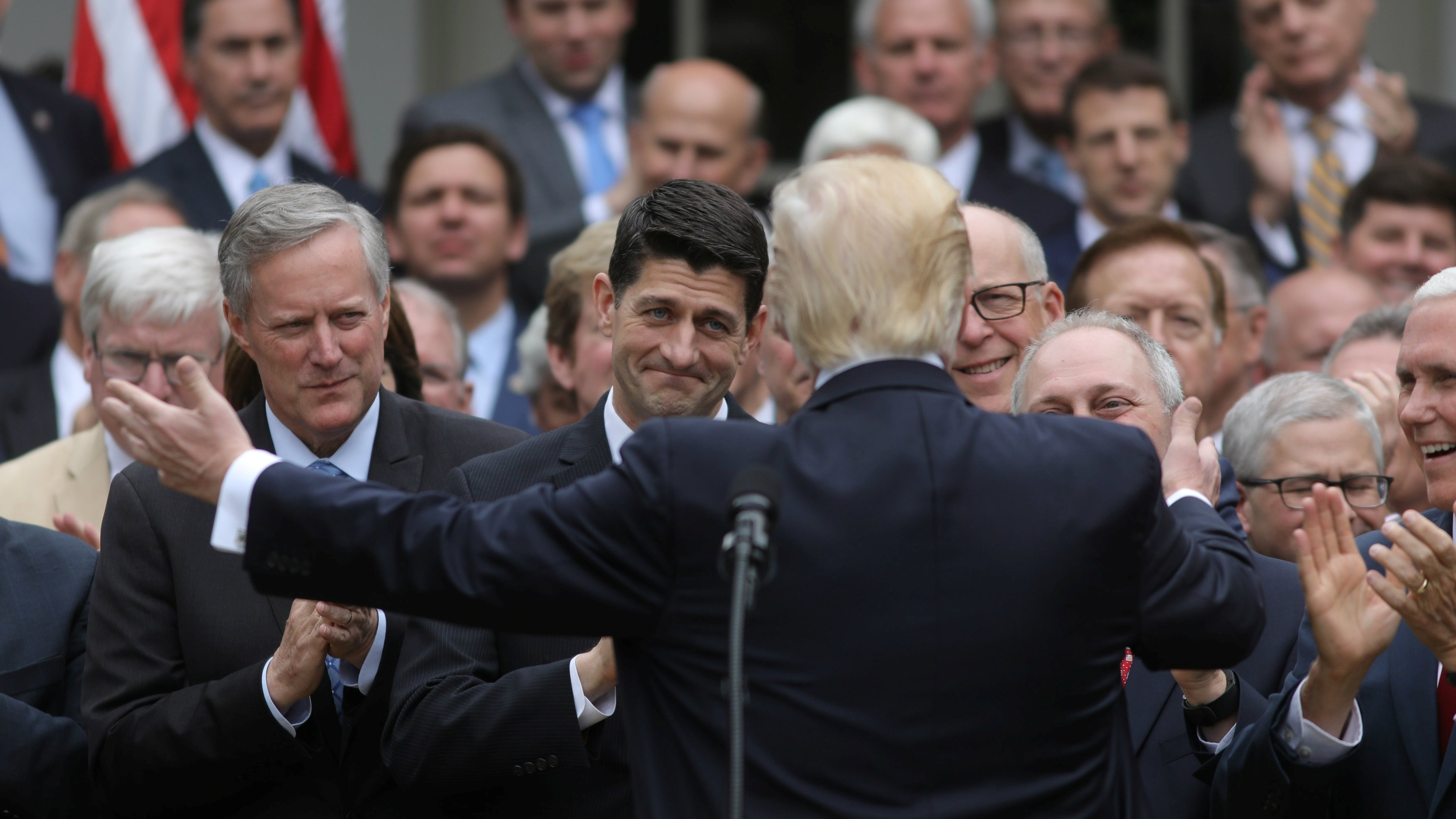 U.S. President Donald Trump (C) turns to House Speaker Paul Ryan (3rdL) as he gathers with Congressional Republicans in the Rose Garden of the White House after the House of Representatives approved the American Healthcare Act, to repeal major parts of Obamacare and replace it with the Republican healthcare plan, in Washington, U.S., May 4, 2017. REUTERS/Carlos Barria TPX IMAGES OF THE DAY