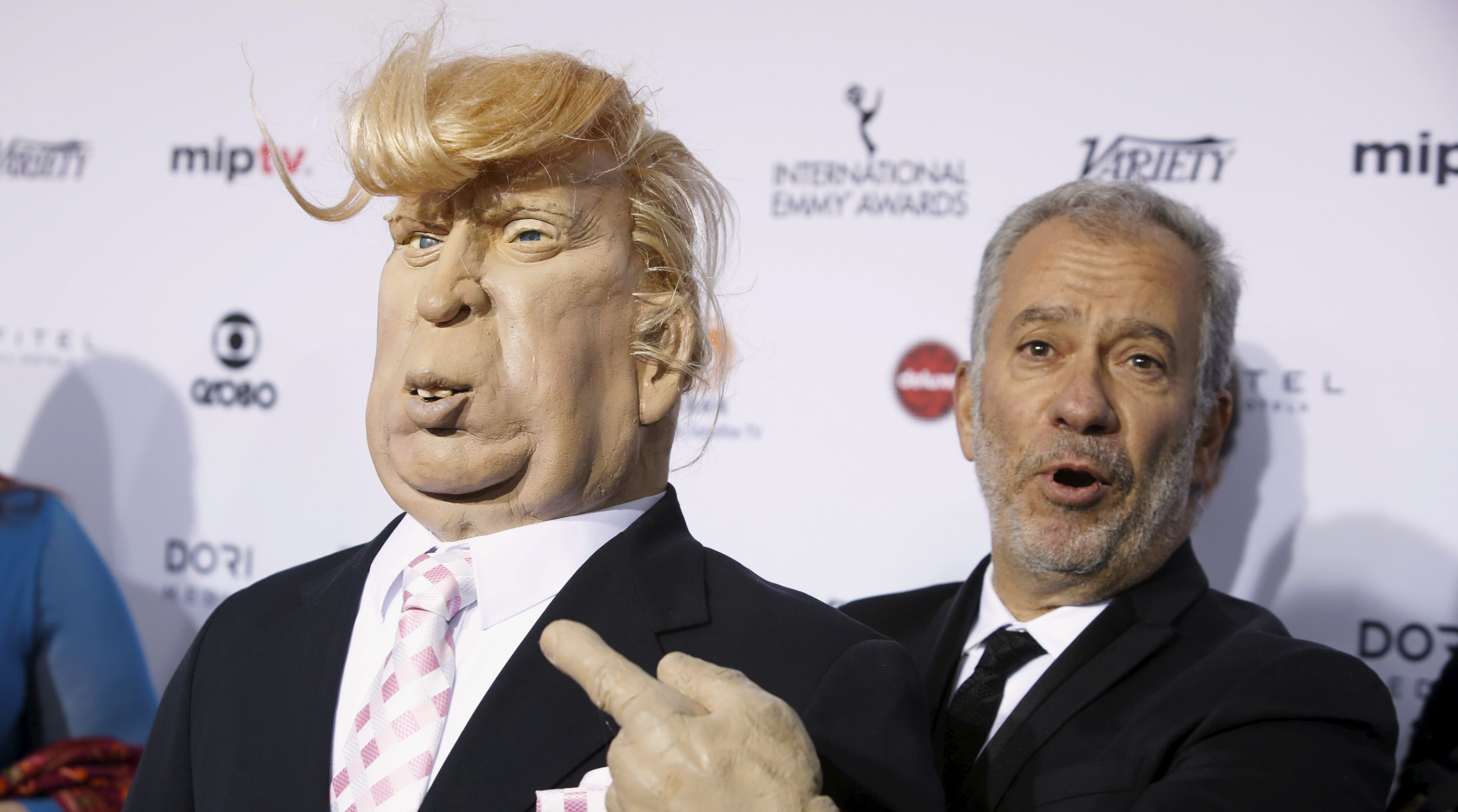 South Africa-based television producer Thierry Cassuto (R) holds a puppet of U.S businessman and Republican Presidential candidate Donald Trump as he attends the International Emmy Awards in Manhattan, New York November 23, 2015.