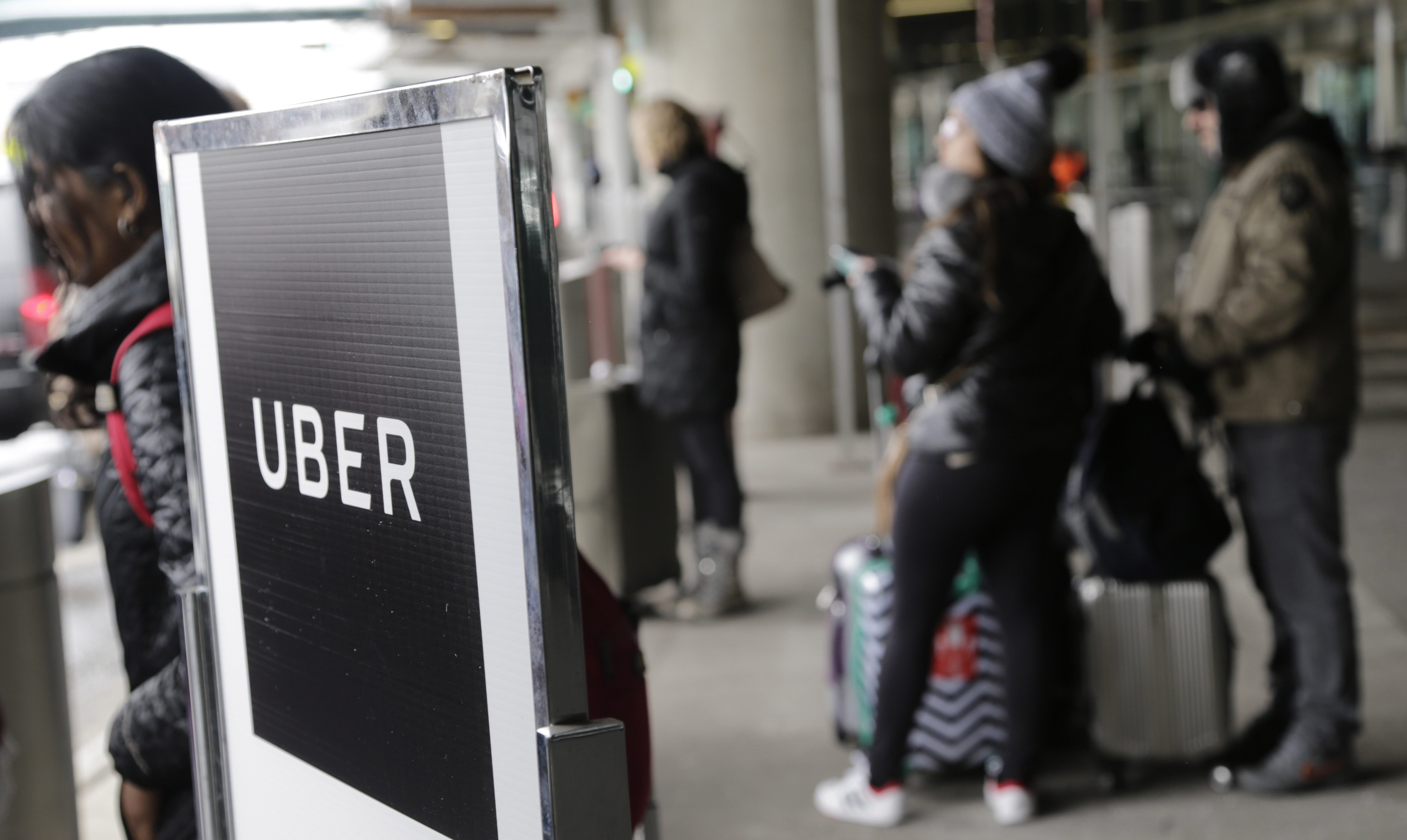 A sign marks a pick-up point for the Uber car service at LaGuardia Airport in New York, Wednesday, March 15, 2017.  (AP Photo/Seth Wenig)