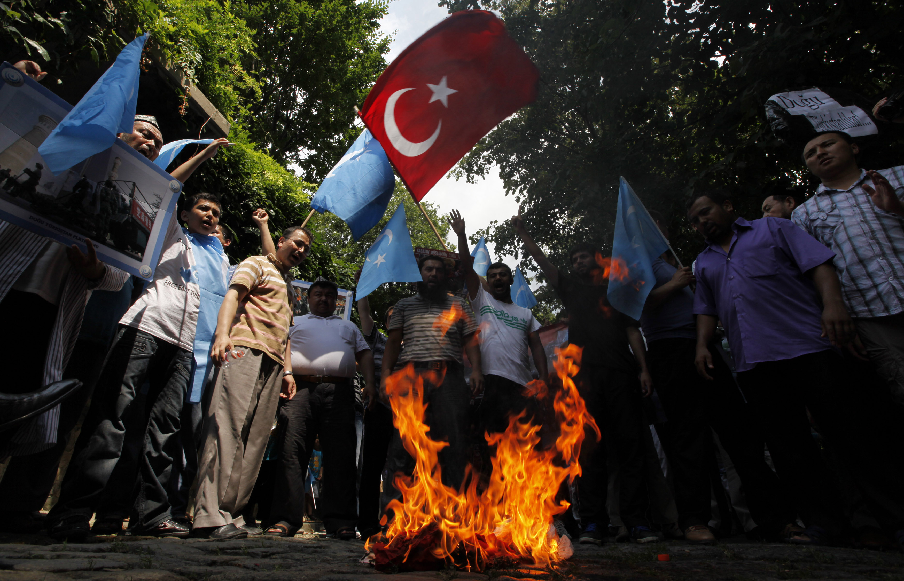 """Ethnic Uighur demonstrators, waving Turkish and blue East Turkestan flags, set fire to a Chinese flag during a protest against China near the Chinese Consulate in Istanbul July 21, 2011. China on Wednesday raised the death toll to 18 from a clash at a police station in the restive far western region of Xinjiang, saying that 14 """"rioters"""" died along with two policemen and two hostages in the worst violence there in a year. Government officials previously said at least four people were killed in what they described as a terrorist attack. But the Germany-based exile group World Uyghur Congress said it was an attack on unarmed protesters."""