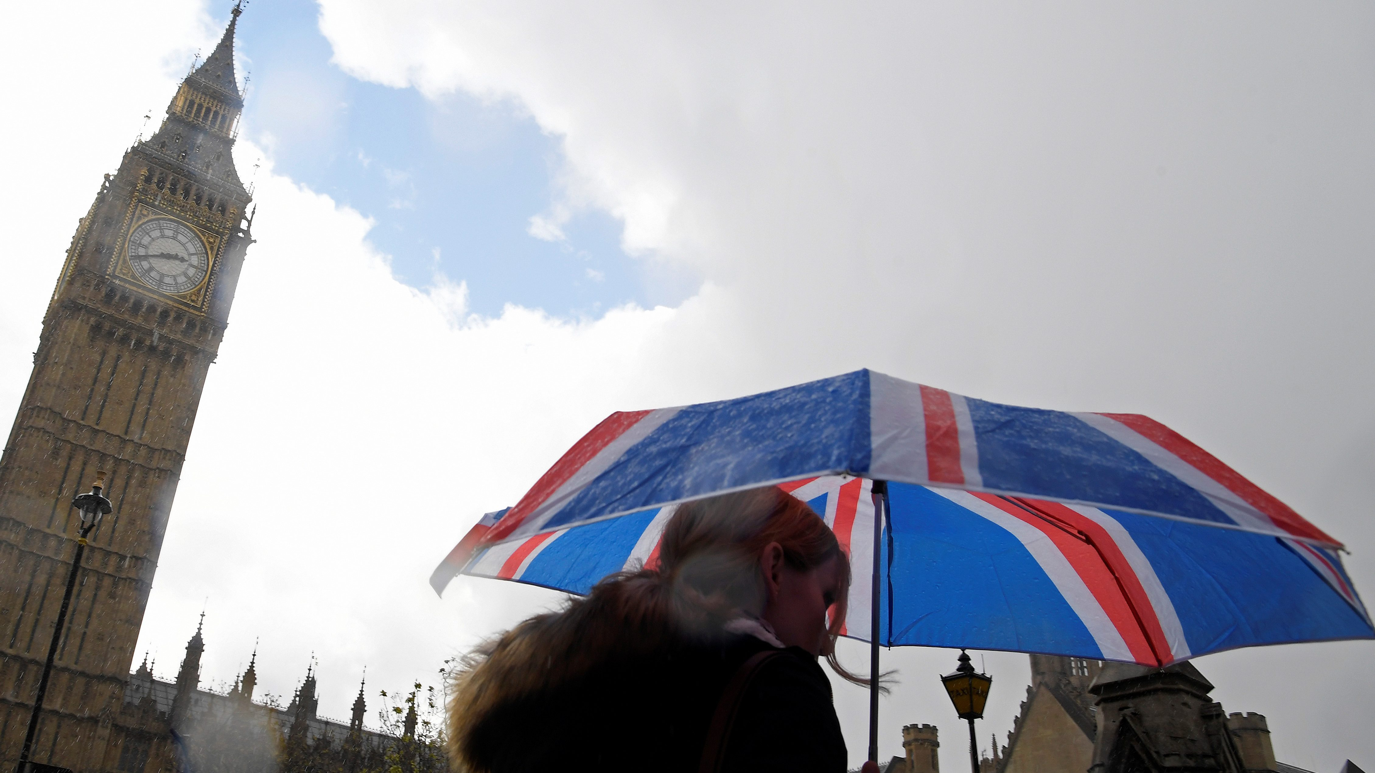 A woman carries a British union flag design umbrella as she walks past the Houses of Parliament in London, Britain, April 26, 2017.