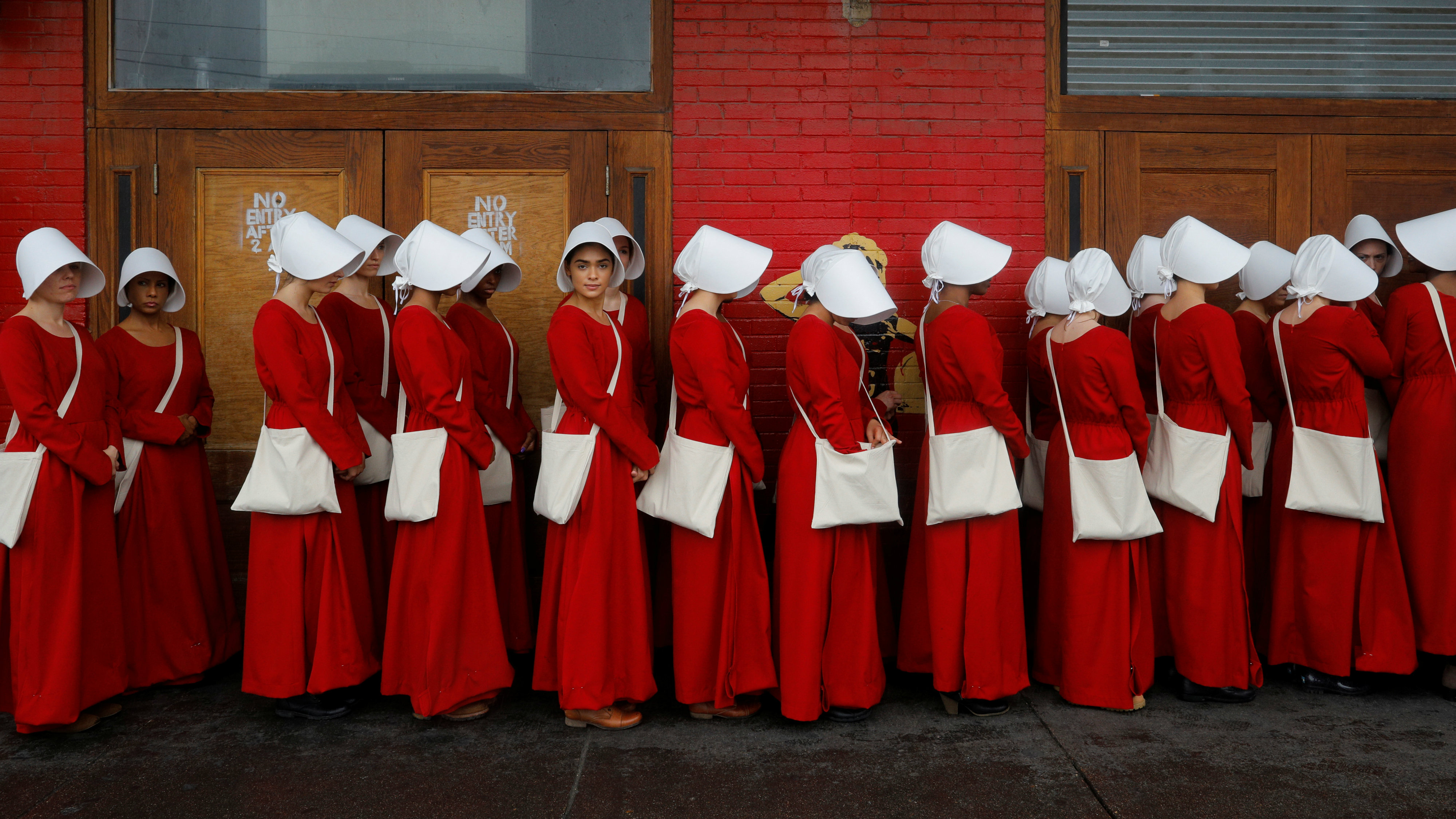 """Women dressed as handmaids promoting the Hulu original series """"The Handmaid's Tale"""" stand along a public street during the South by Southwest (SXSW) Music Film Interactive Festival 2017 in Austin, Texas, U.S., March 11, 2017. REUTERS/Brian Snyder"""