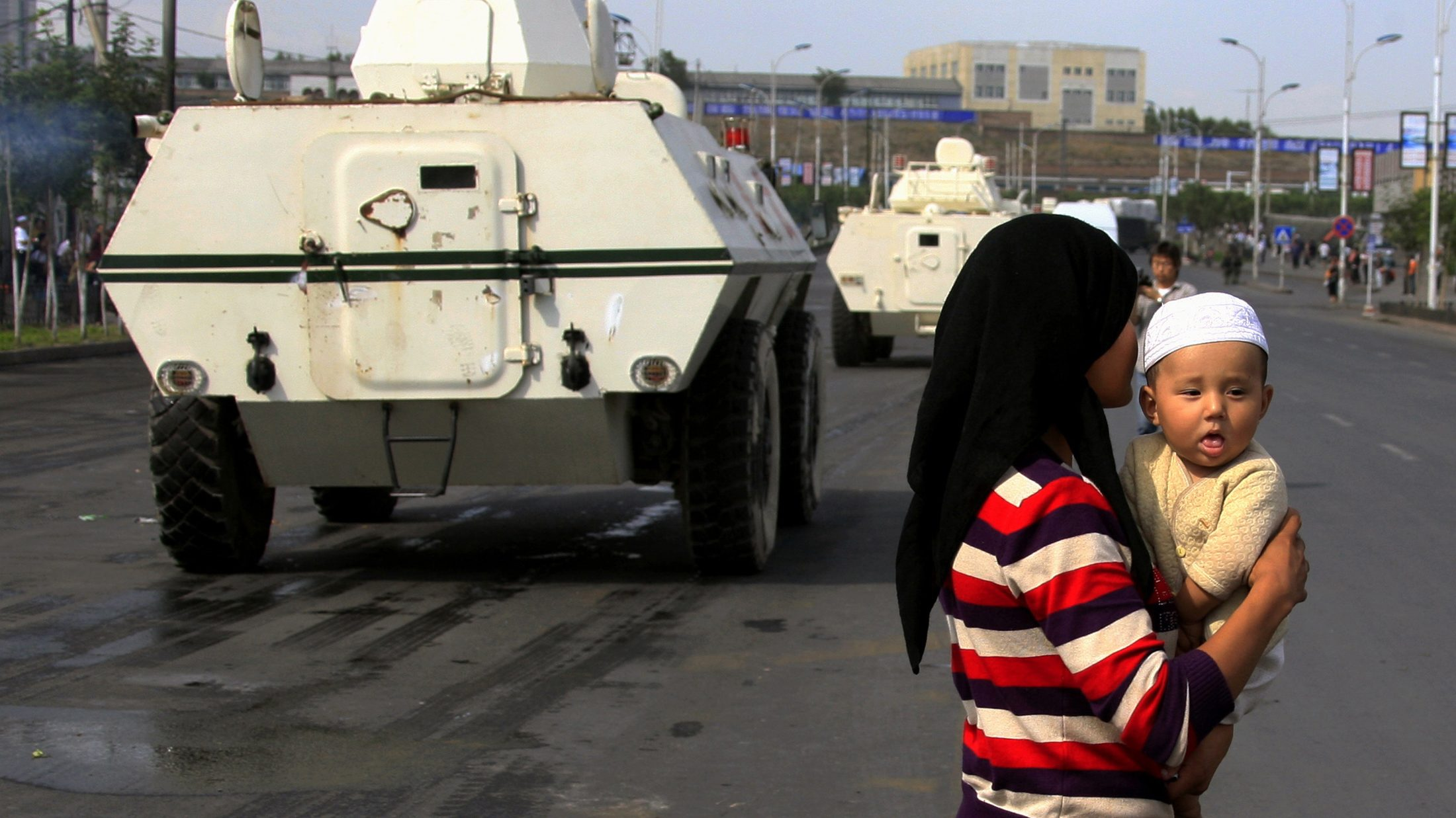 An ethnic Uighur woman carries her child across the road as Chinese armoured personnel carriers drive past in the city of Urumqi in China's Xinjiang Autonomous Region July 12, 2009.