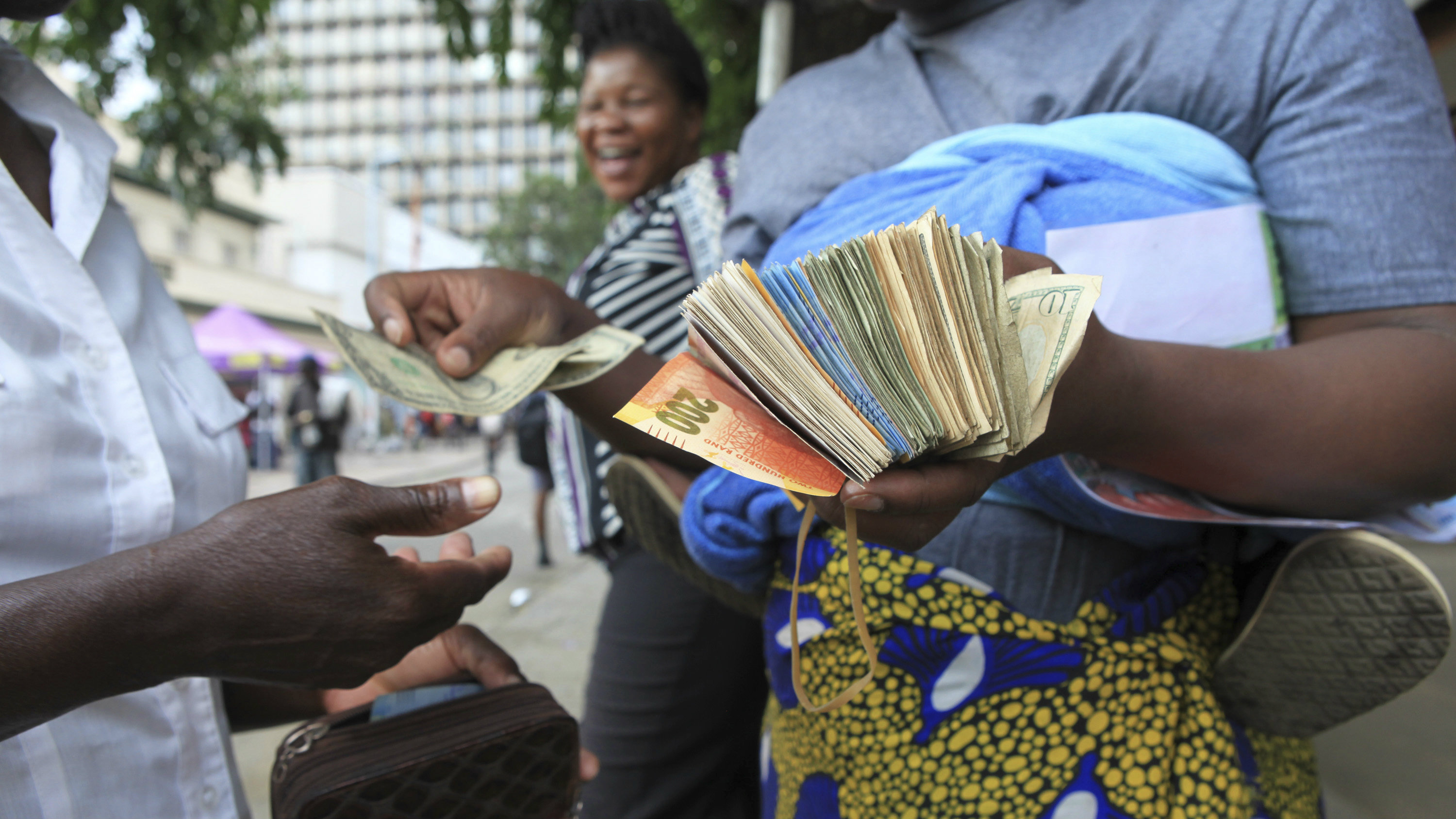 A currency trader performs a transaction on the streets of Harare in this Friday, Oct. 28, 2016 photo.