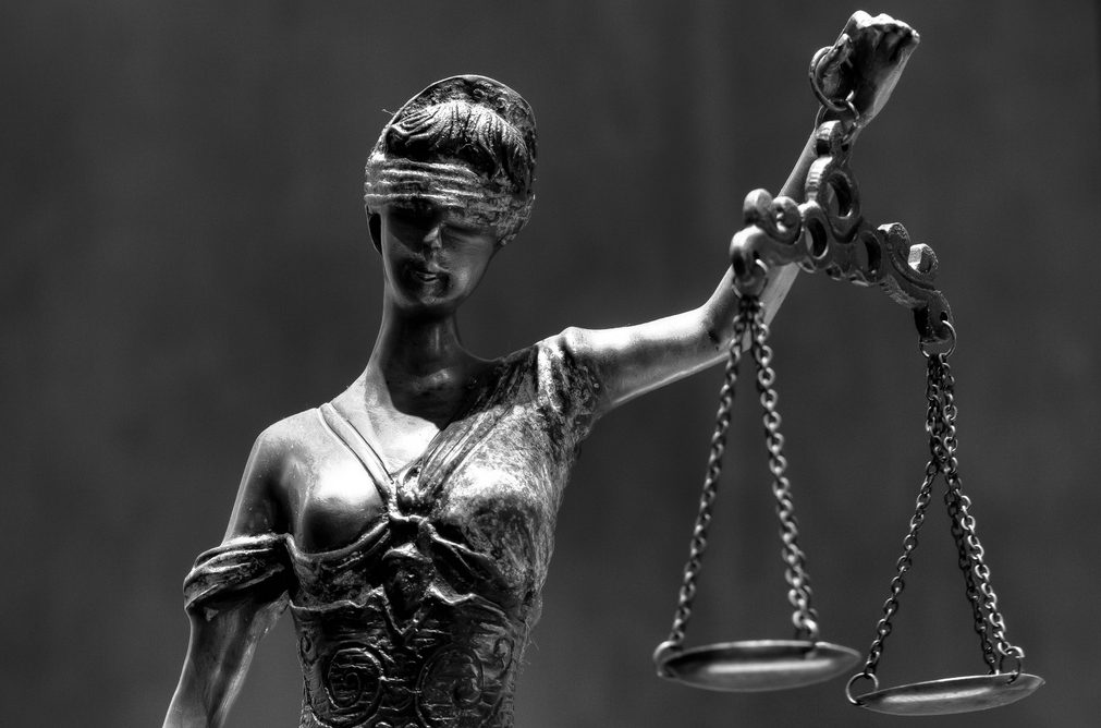 A sculpture of lady blind justice stands with her eyes blindfolded and a scale in her hand.