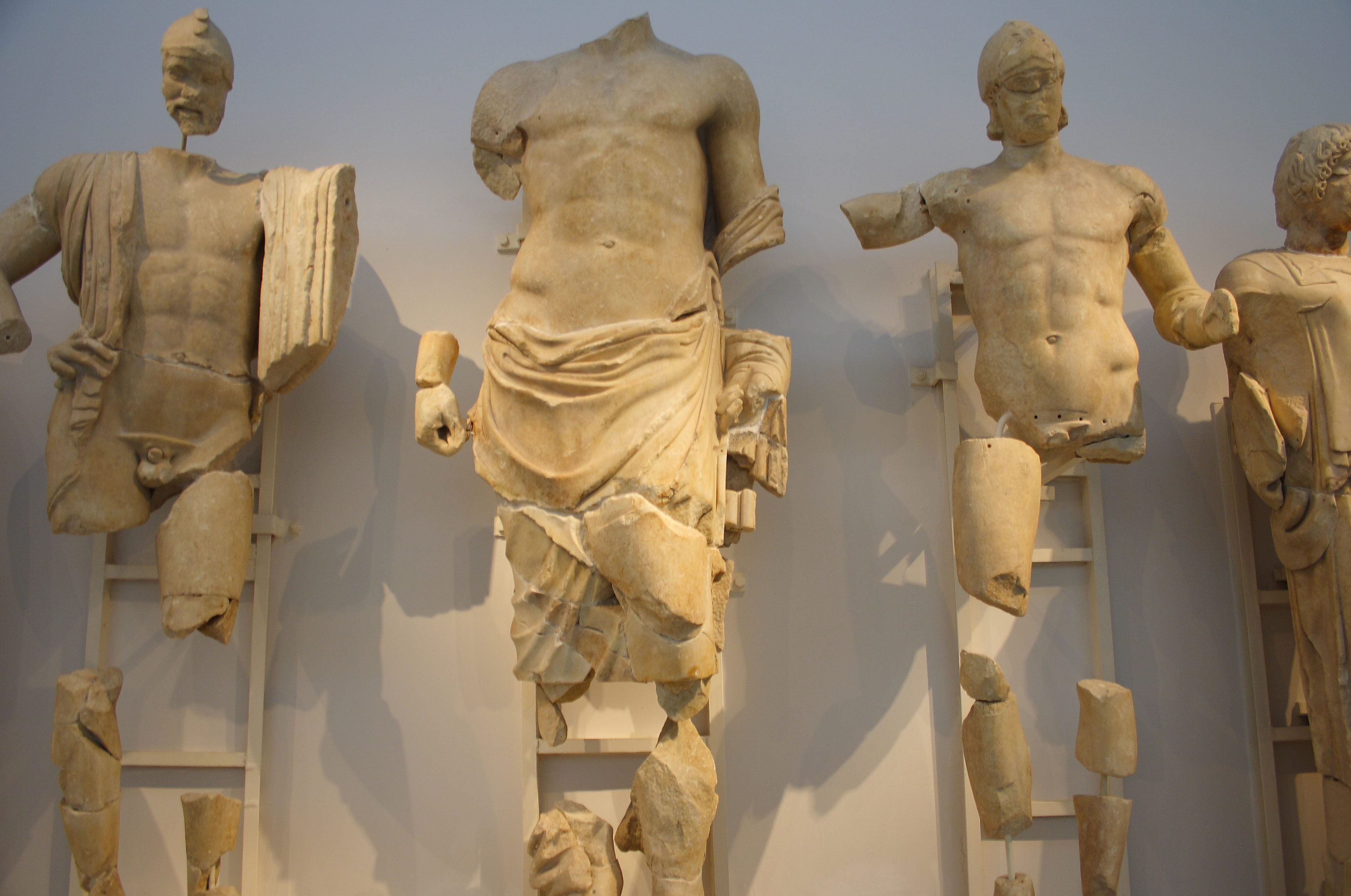 4 statues that have been fractured are reassembled against a wall. All of these statues are white marble men sculpted in the classical style.
