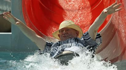 An older man slides down a water slide.