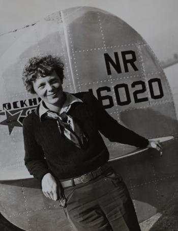 Amelia Earhart in front of a plane.
